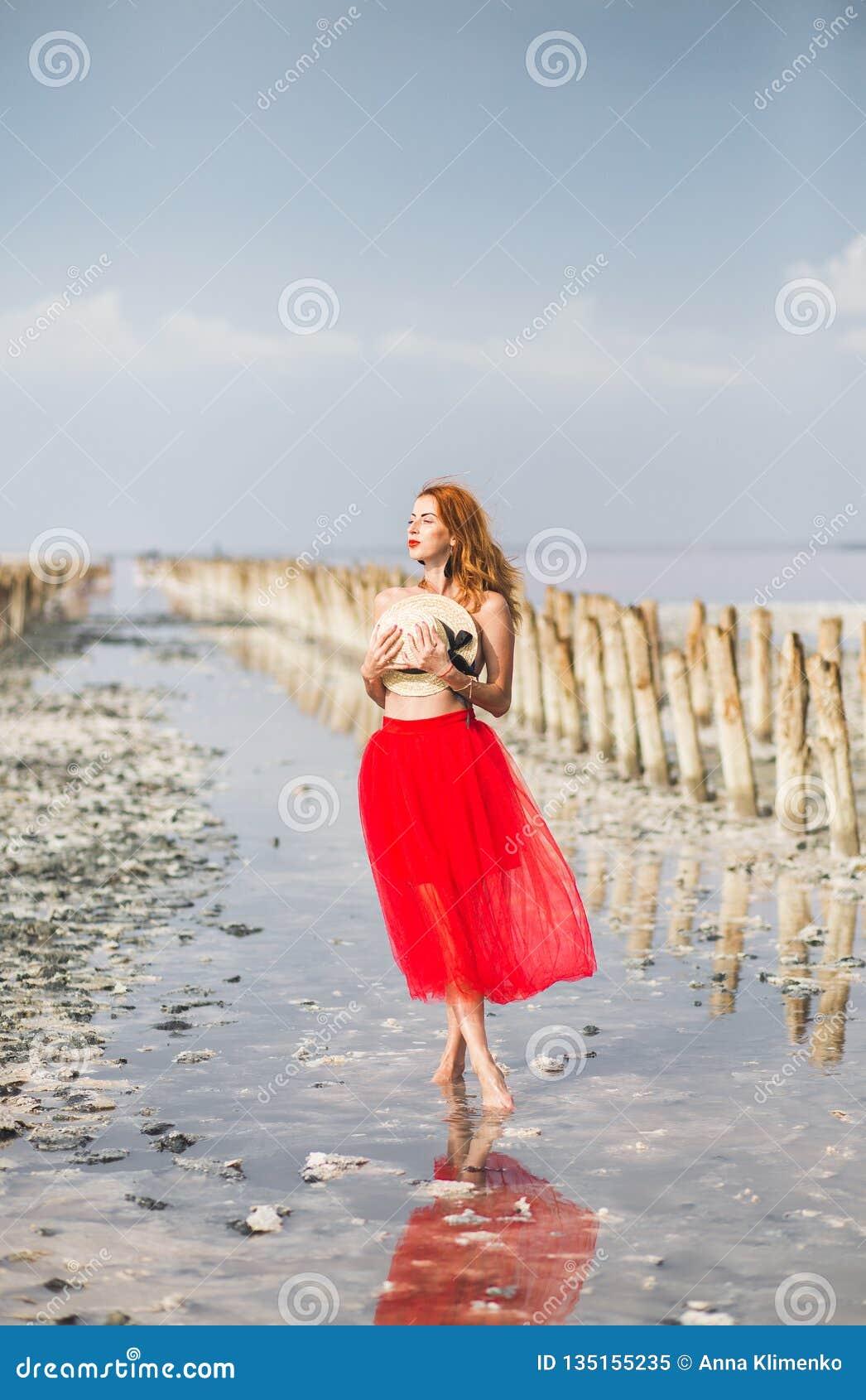Красивая рыжеволосая маленькая девочка на пляже