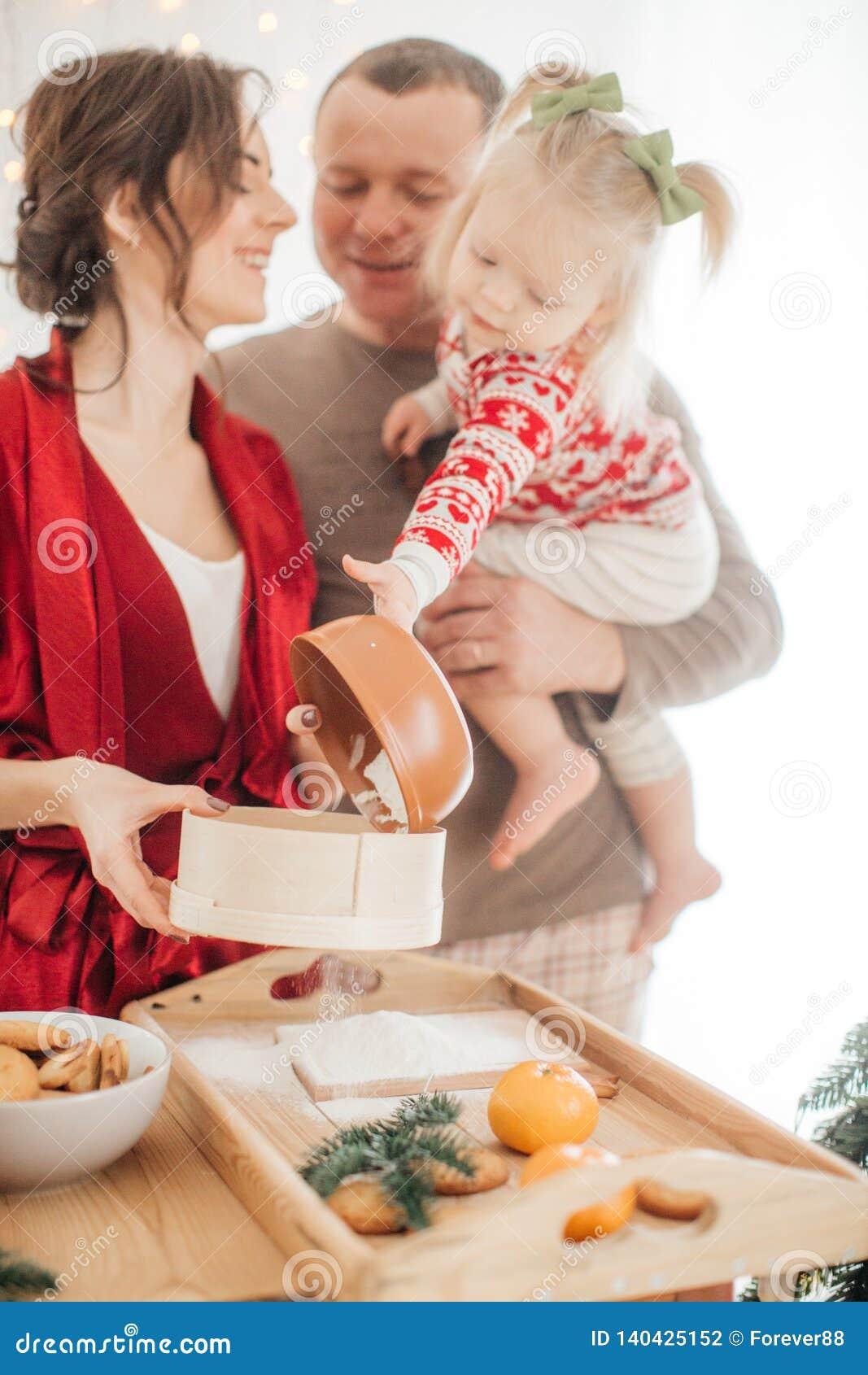 Красивая семья с ребенком подготавливая тесто для пирога