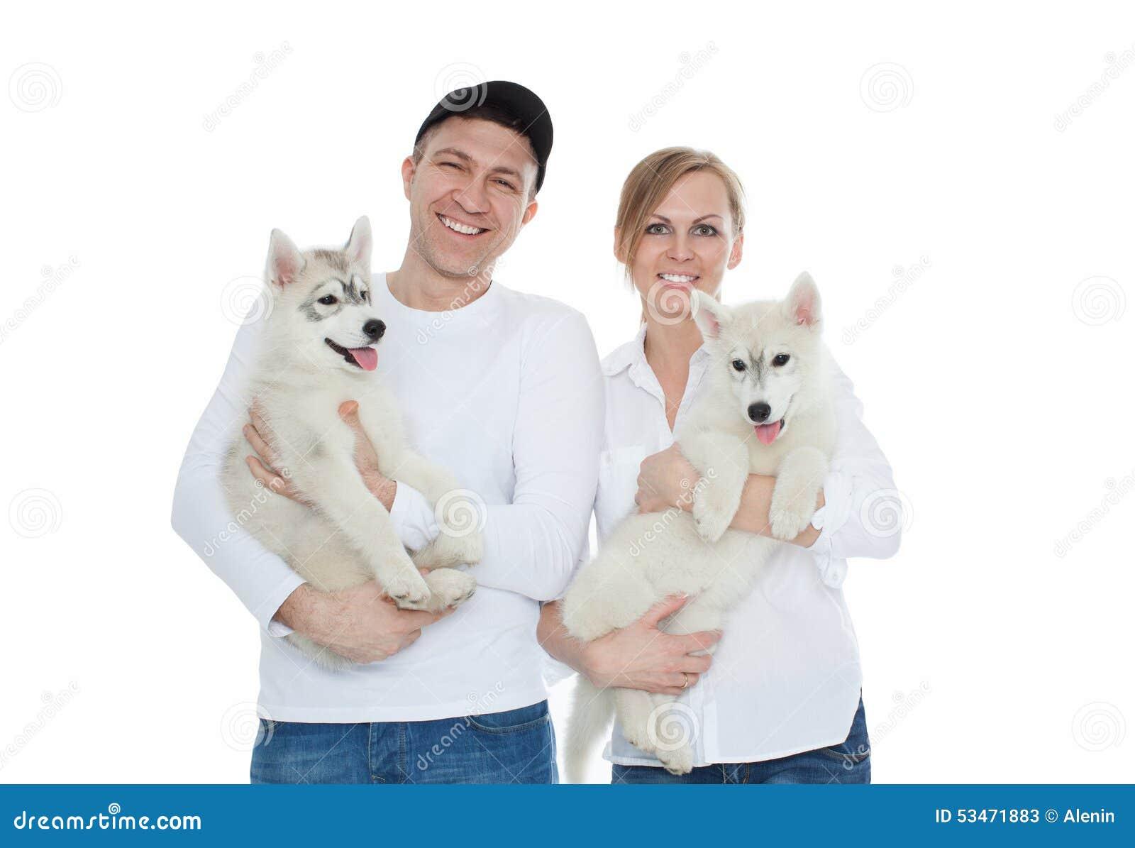 Красивая семья, человек и женщина держа руки на осиплых щенятах, изоляцию