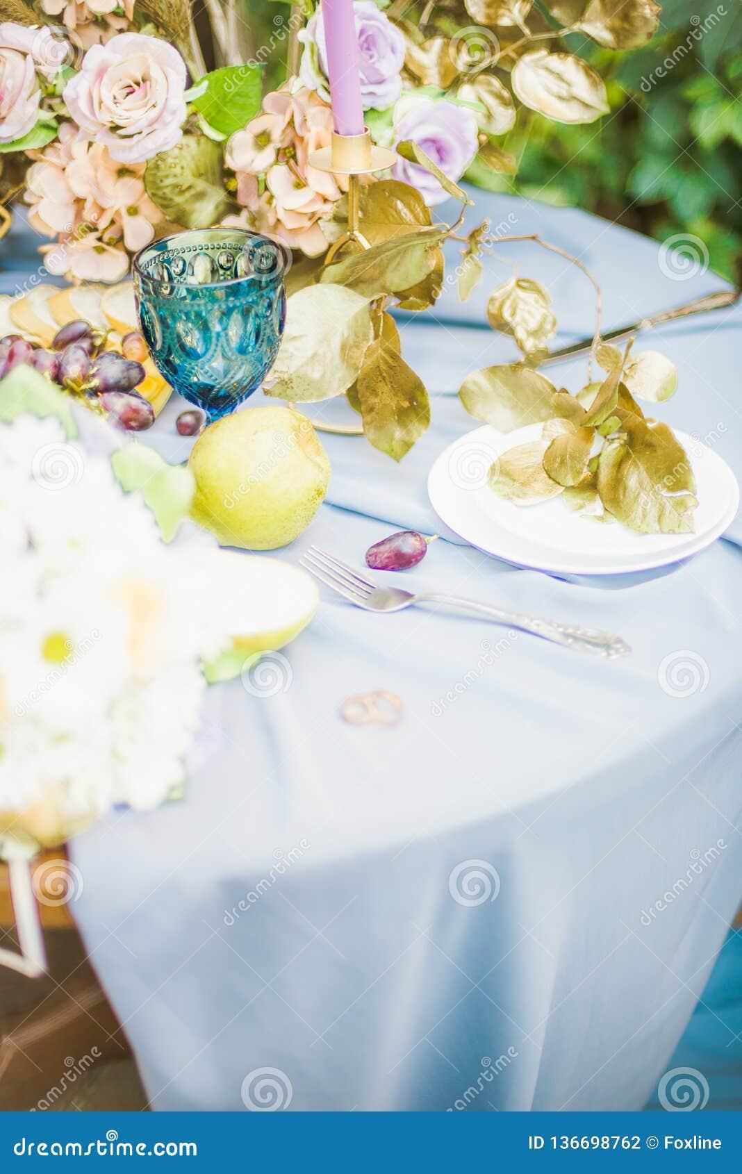 Красивая сервировка стола с посудой и цветками для партии, приема по случаю бракосочетания