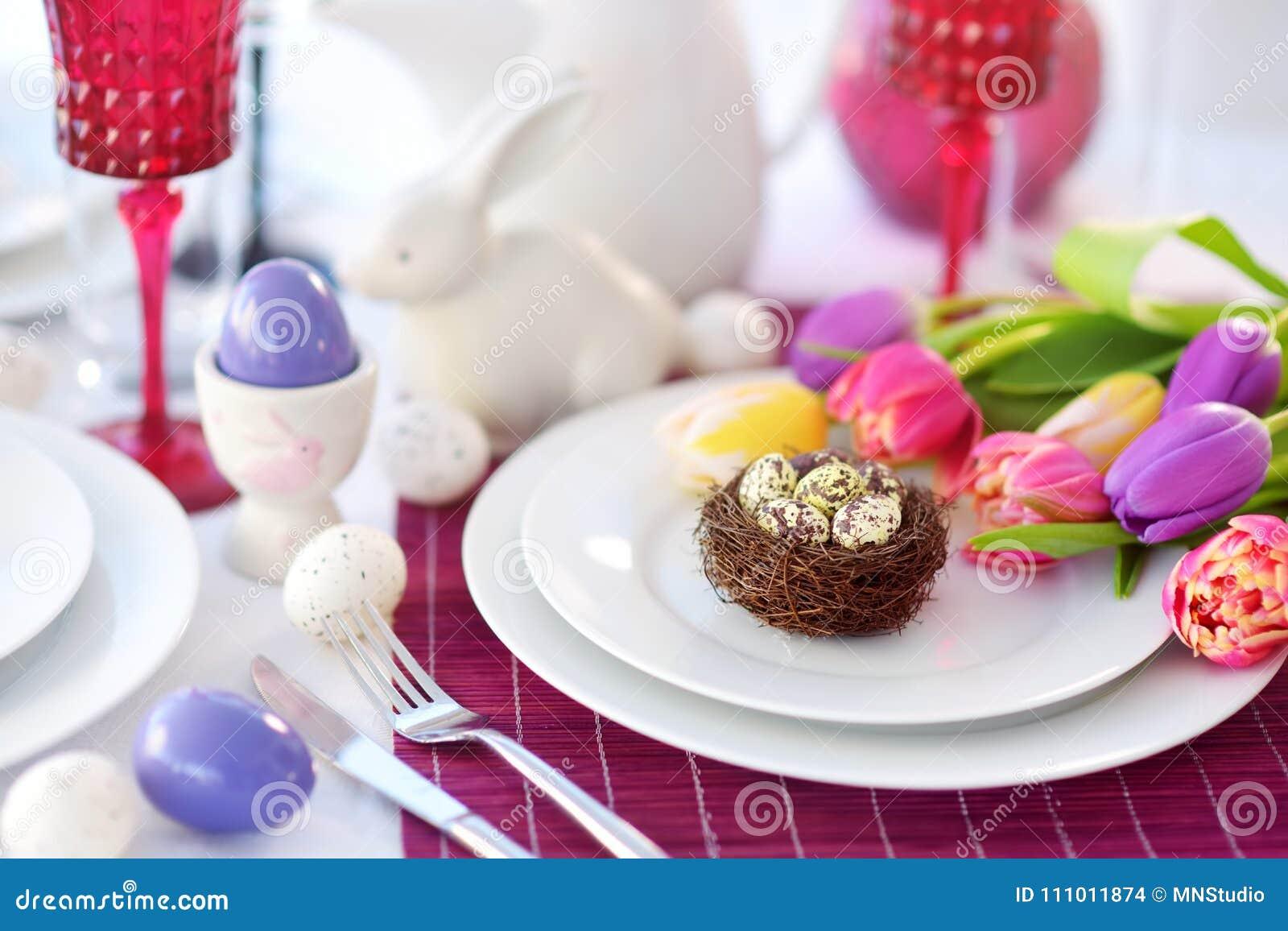 Красивая сервировка стола с посудой и цветками для торжества пасхи