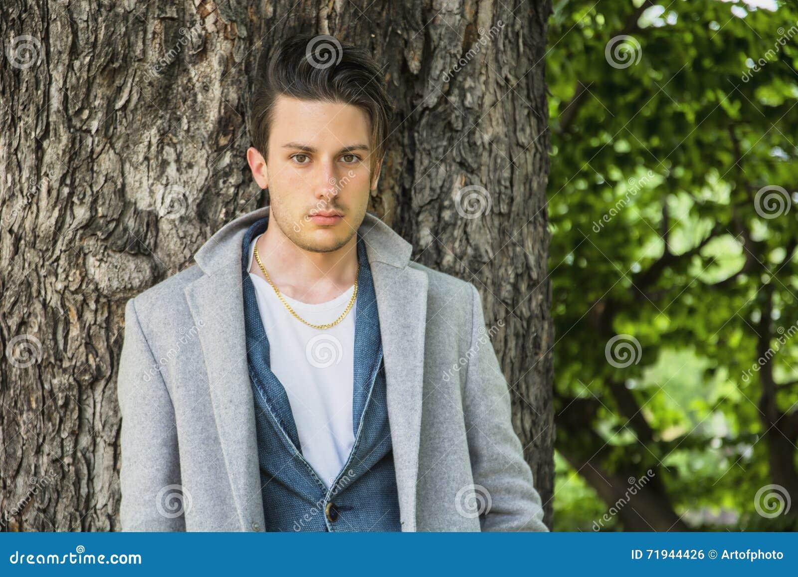 Красивая склонность молодого человека против дерева