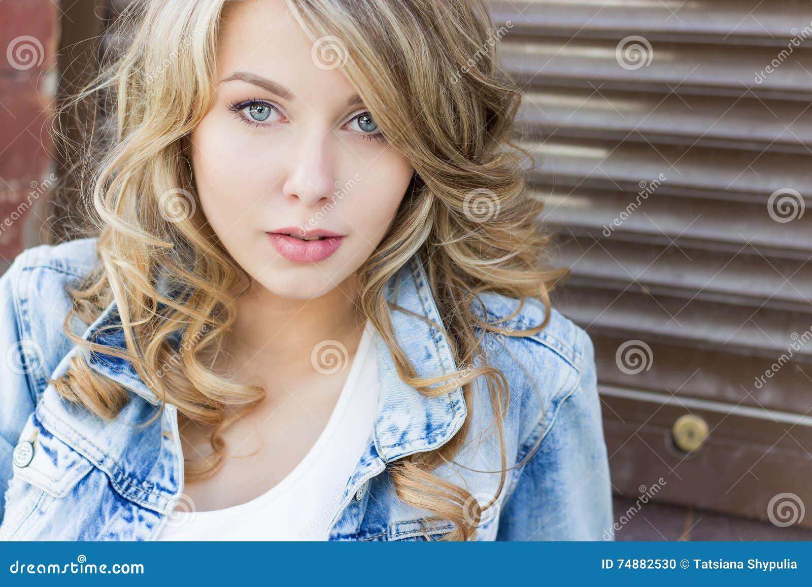 Красивая смешная белокурая девушка с большими губами с очаровательными джинсами улыбки, носить и белой рубашкой идя в solnetsnym
