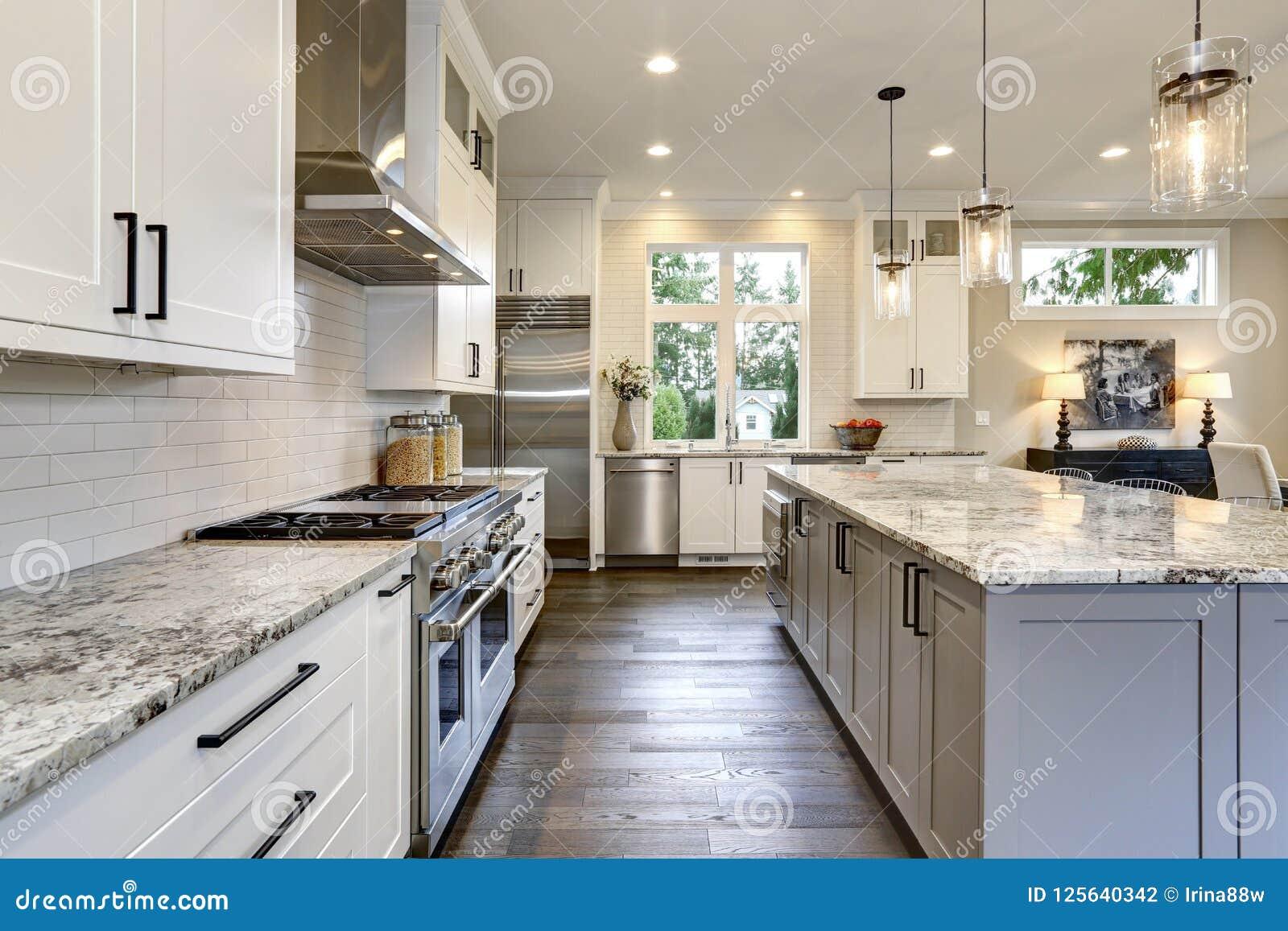 Красивая современная кухня в роскошном домашнем интерьере с островом и