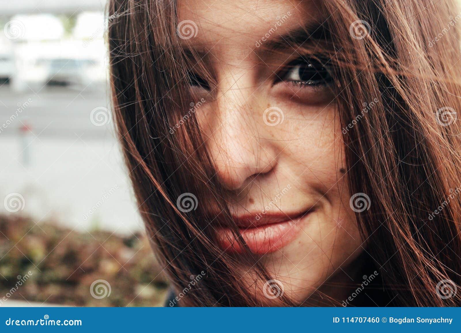 Красивая стильная девушка брюнет усмехаясь с веснушками на backgro