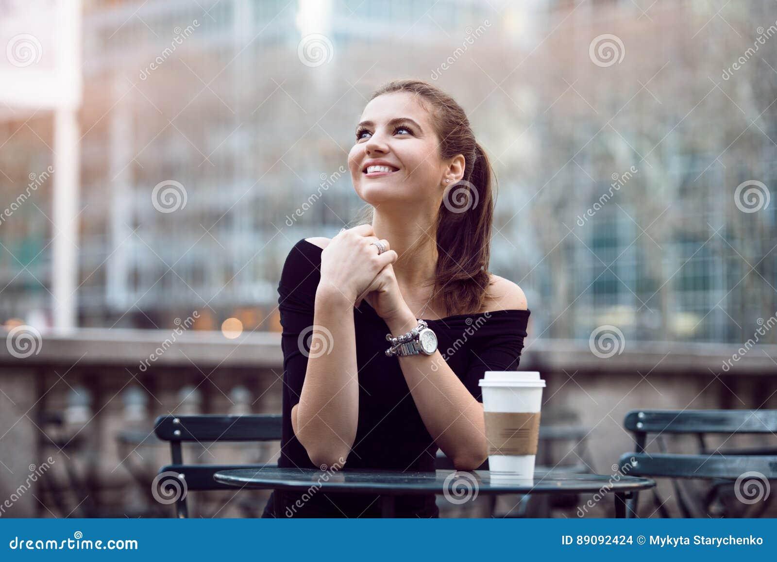 Красивая счастливая коммерсантка сидя в парке города во время времени обеда или перерыве на чашку кофе с бумажной кофейной чашкой
