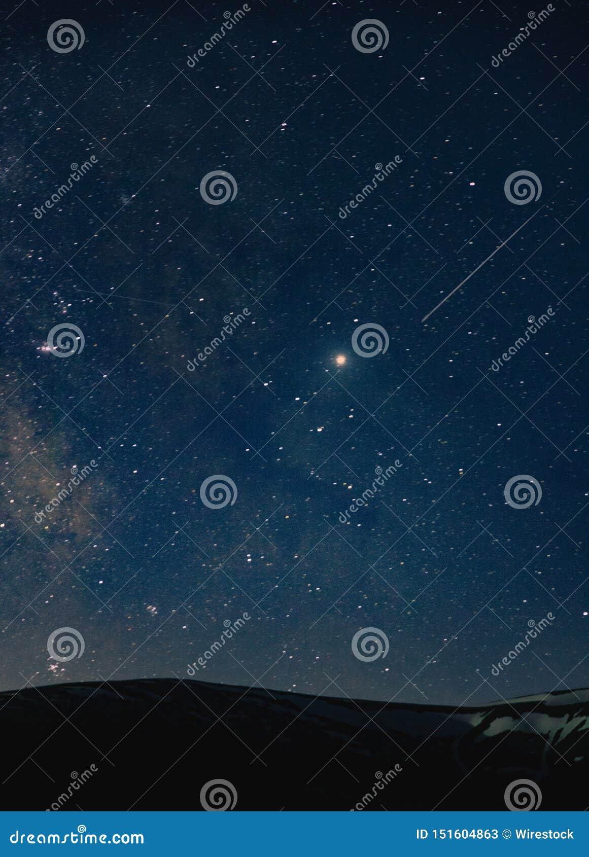 Красивая съемка изумительного неба вполне захватывающих звезд вечером над холмами