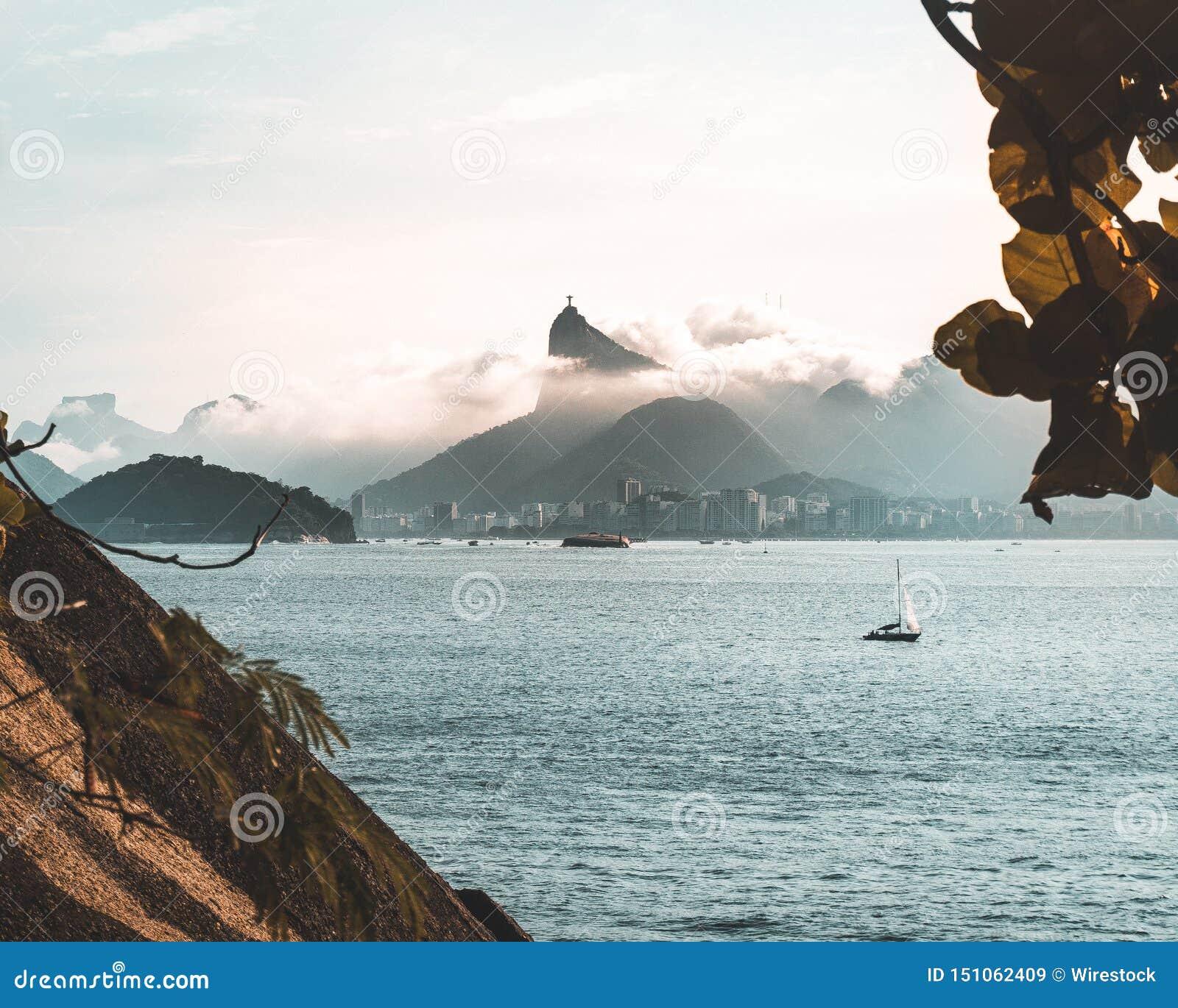 Красивая съемка моря со шлюпкой в воде и изумляя пасмурных холмах на заднем плане