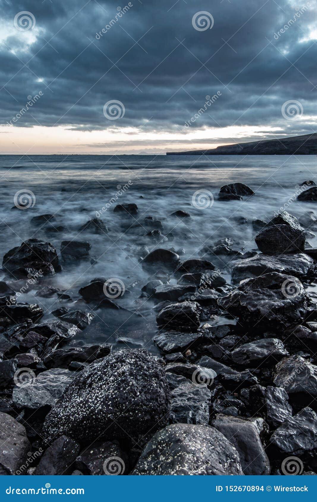 Красивая съемка скалистого побережья моря с изумляя текстурой воды и захватывающим пасмурным серым небом