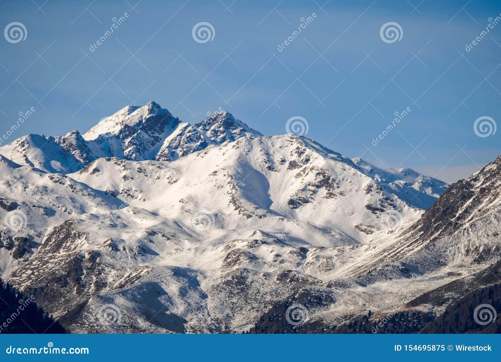 Красивая съемка снег-покрытой горы на солнечный день с ясным небом на заднем плане