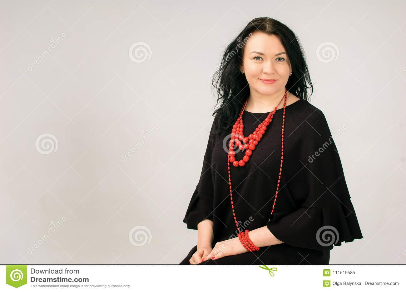Красивая темн-с волосами женщина касается ее волосам Большой портрет Она одета в черном платье Она имеет красное этническое
