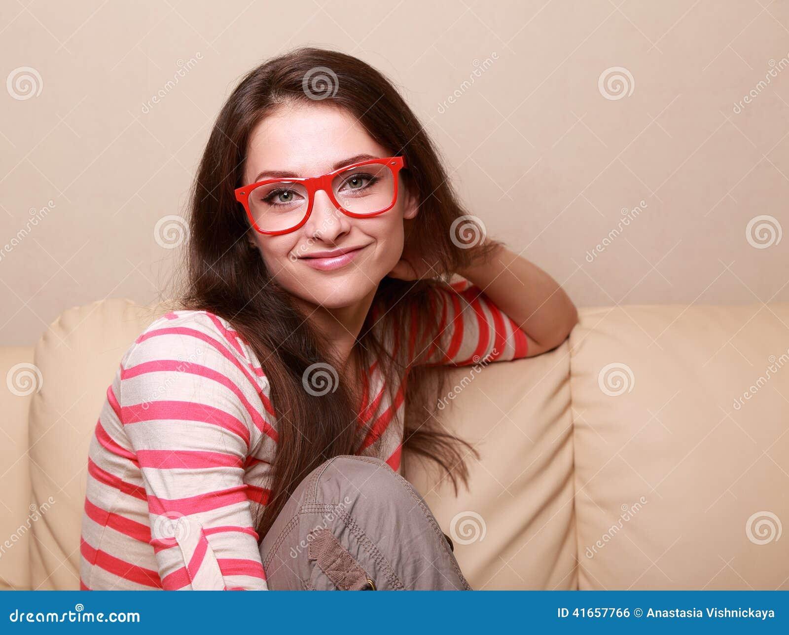 Красивая усмехаясь девушка в красный сидеть стекел