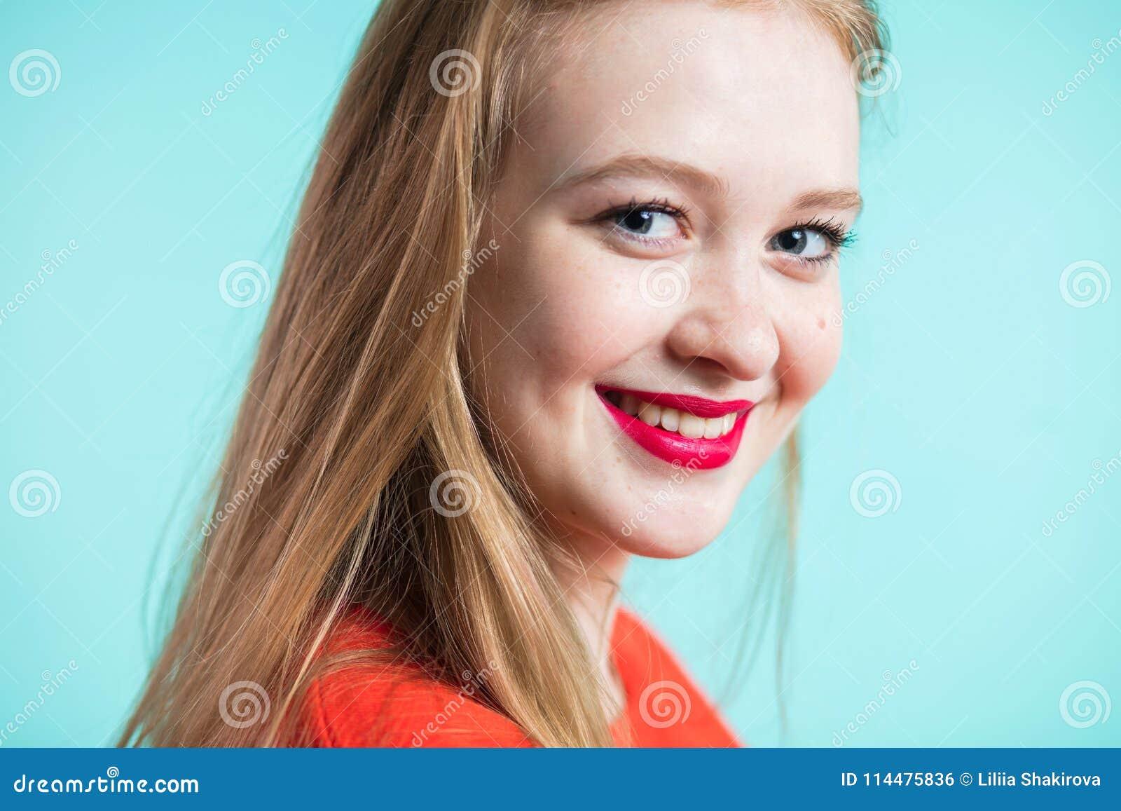 Красивая усмехаясь женщина на предпосылке цвета детеныши портрета девушки крупного плана