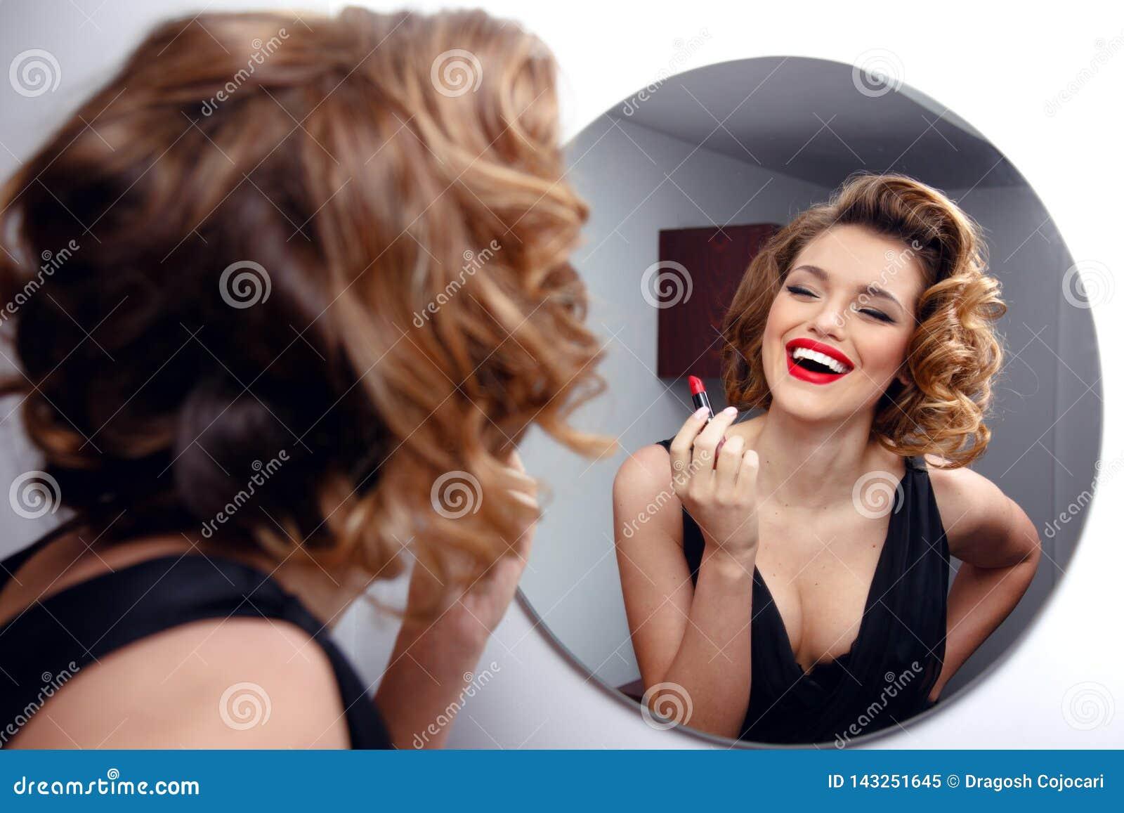 Красивая усмехаясь молодая женщина с идеальным составляет, красные губы, ретро стиль причесок в черном платье, смотря в зеркале