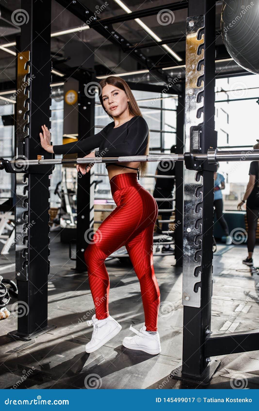 Красивая худенькая девушка в стильных ярких одеждах спорт делает представления рядом с турником в современном спортзале