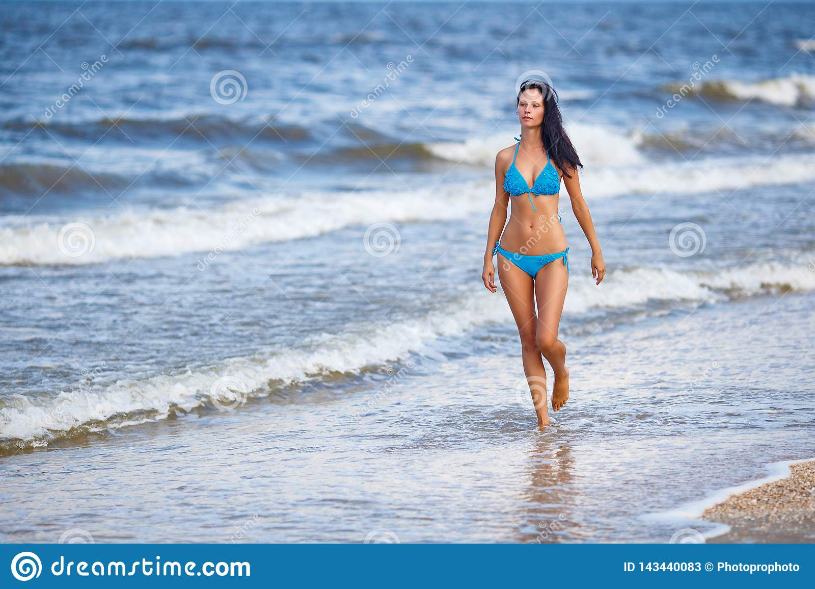 Красивая худенькая женщина в голубом купальнике идя на пляж
