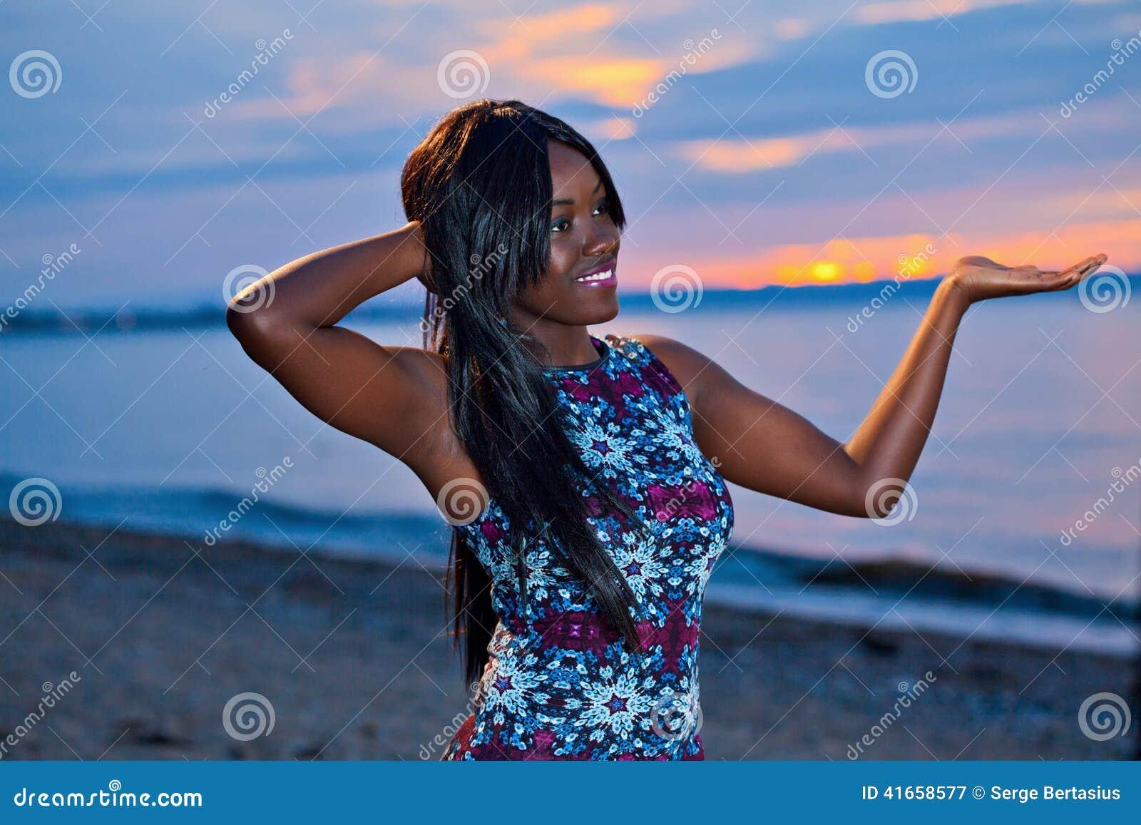 Красивая черная Афро-американская женщина представляя на пляже на su
