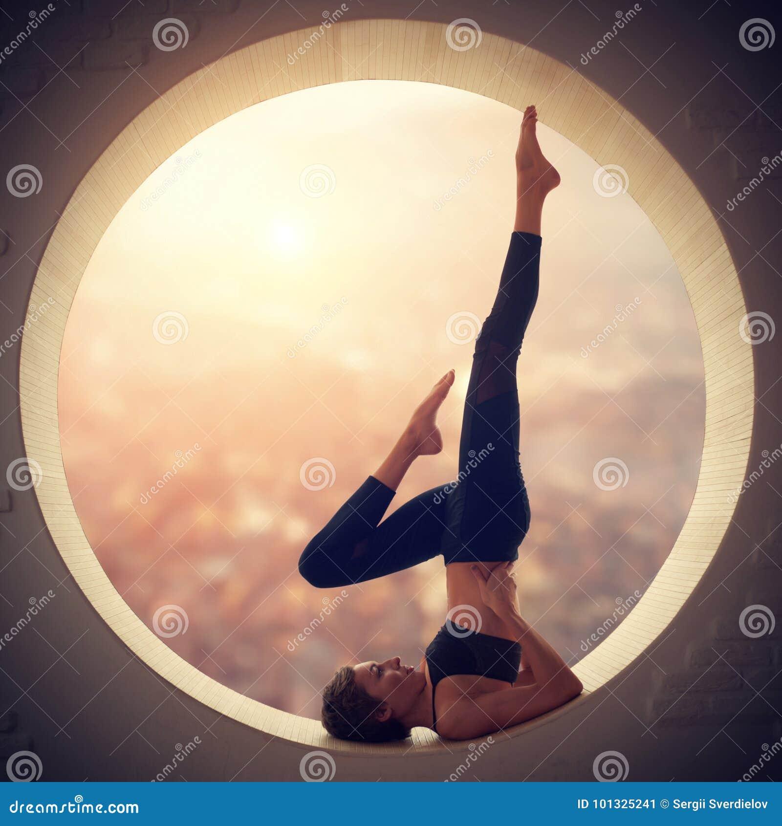 Красивая sporty женщина yogi пригонки практикует йогу Salamba Sarvangasana - представление shoulderstand в окно