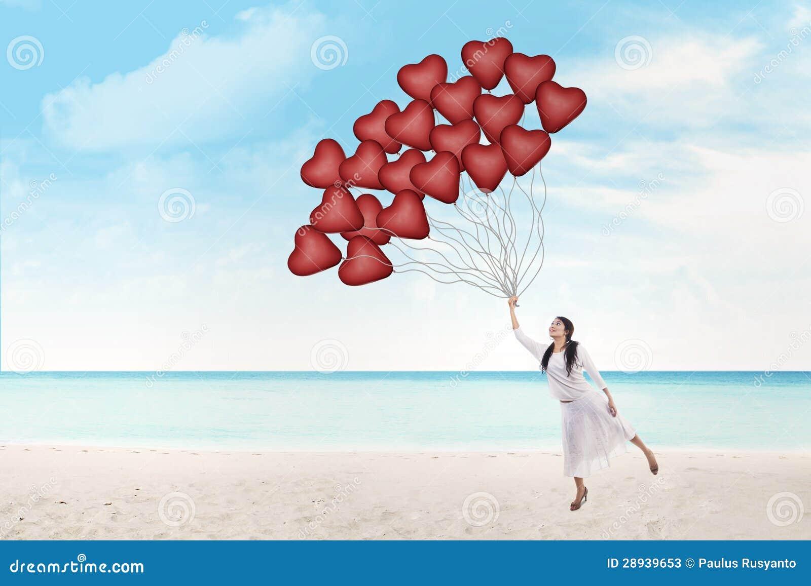 Красивейшая женщина держит воздушные шары сердца