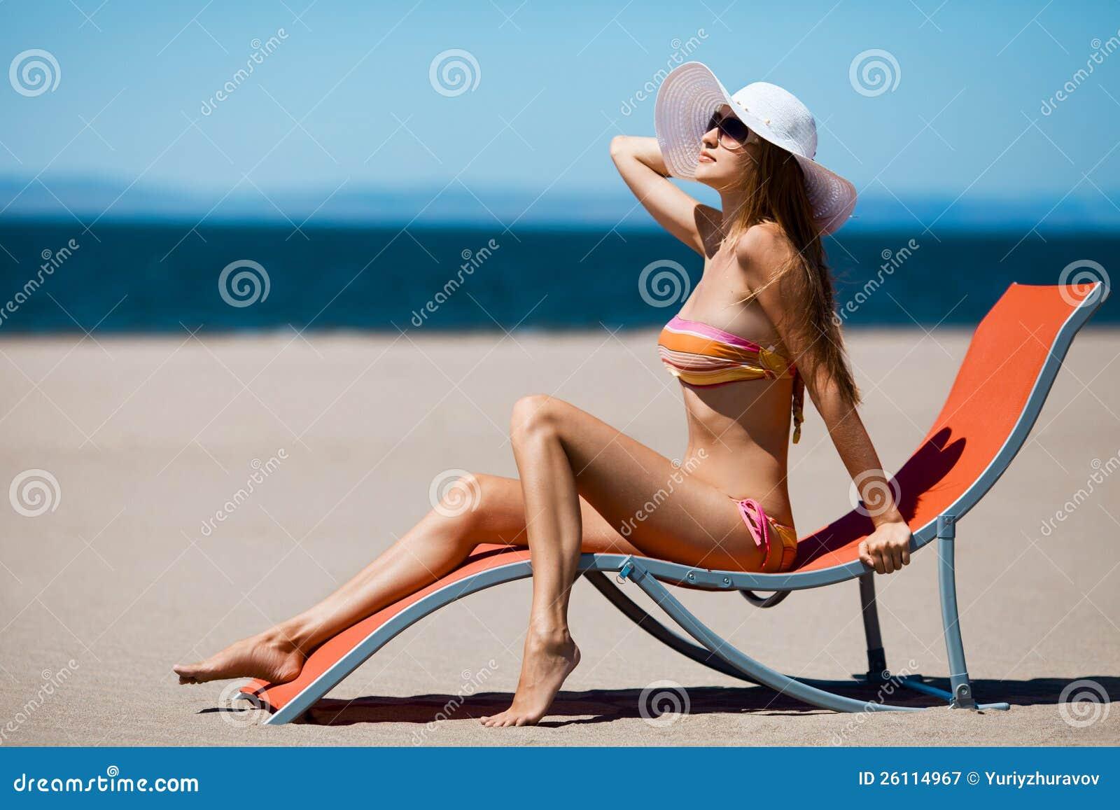 Красивейшая женщина лежа на deckchair на пляже