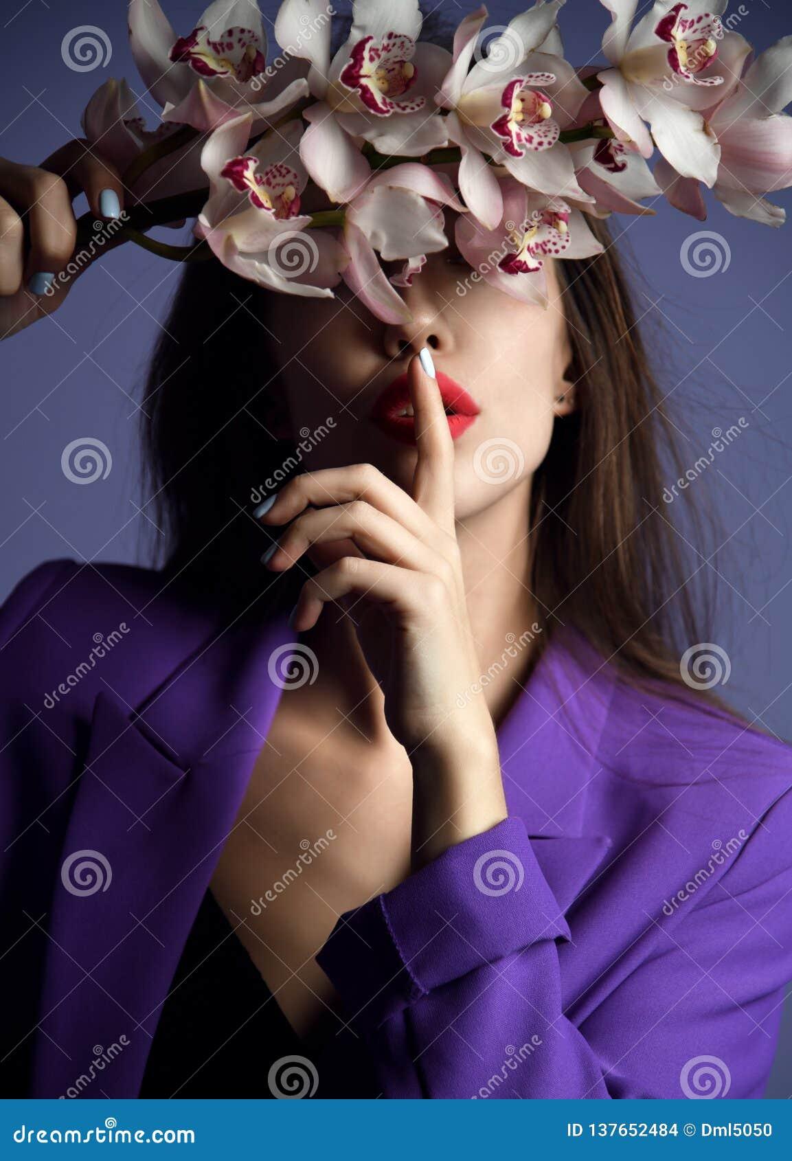 красивейшая орхидея девушки цветков Сторона женщины модели красоты на пурпурной предпосылке