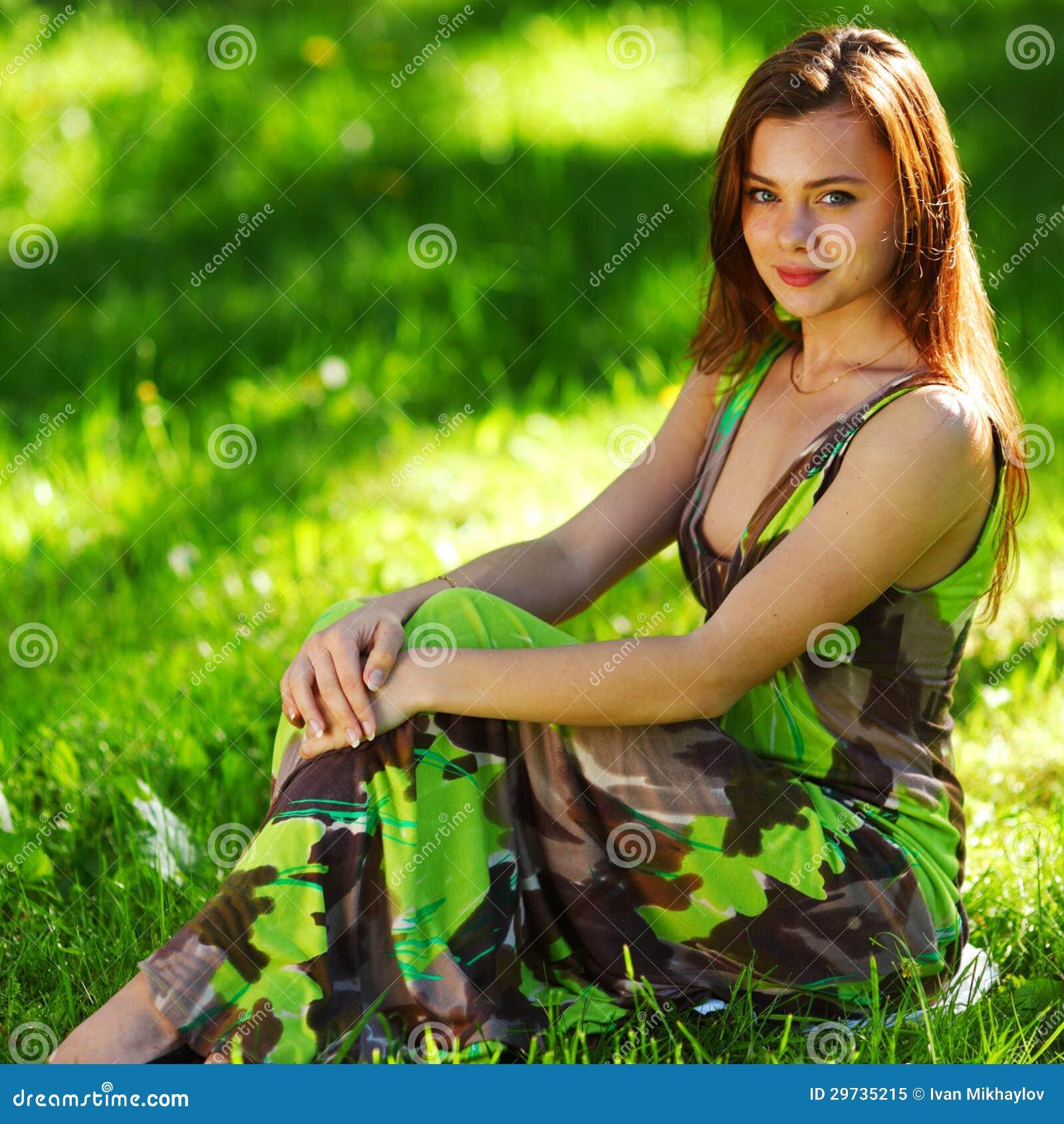 Брюнет сидя на зеленой траве