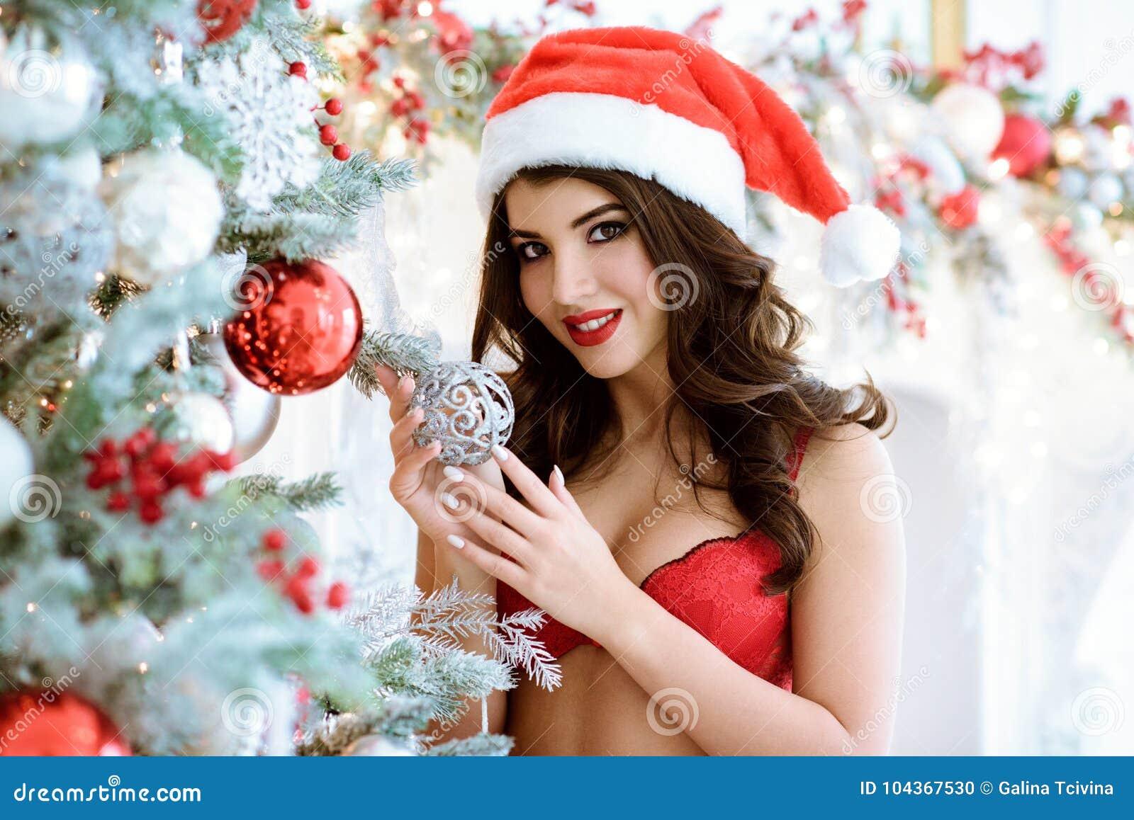 442a2d7870315 Красивое брюнет сексуальный Санта Клаус в элегантных шляпе и бюстгальтере  Фасонируйте портрет модельной девушки внутри помещения с рождественской  елкой ...