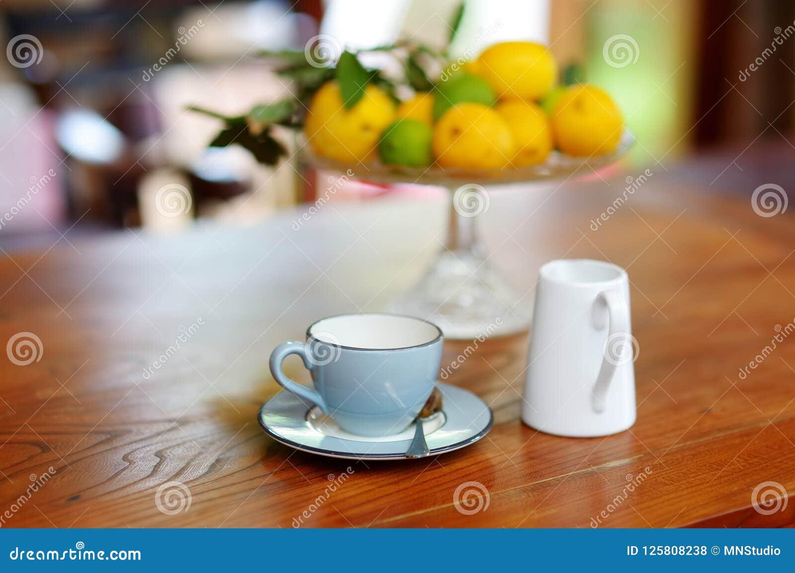 Красивое голубое керамическое чашка на деревянном столе, с блюдом лимонов на предпосылке