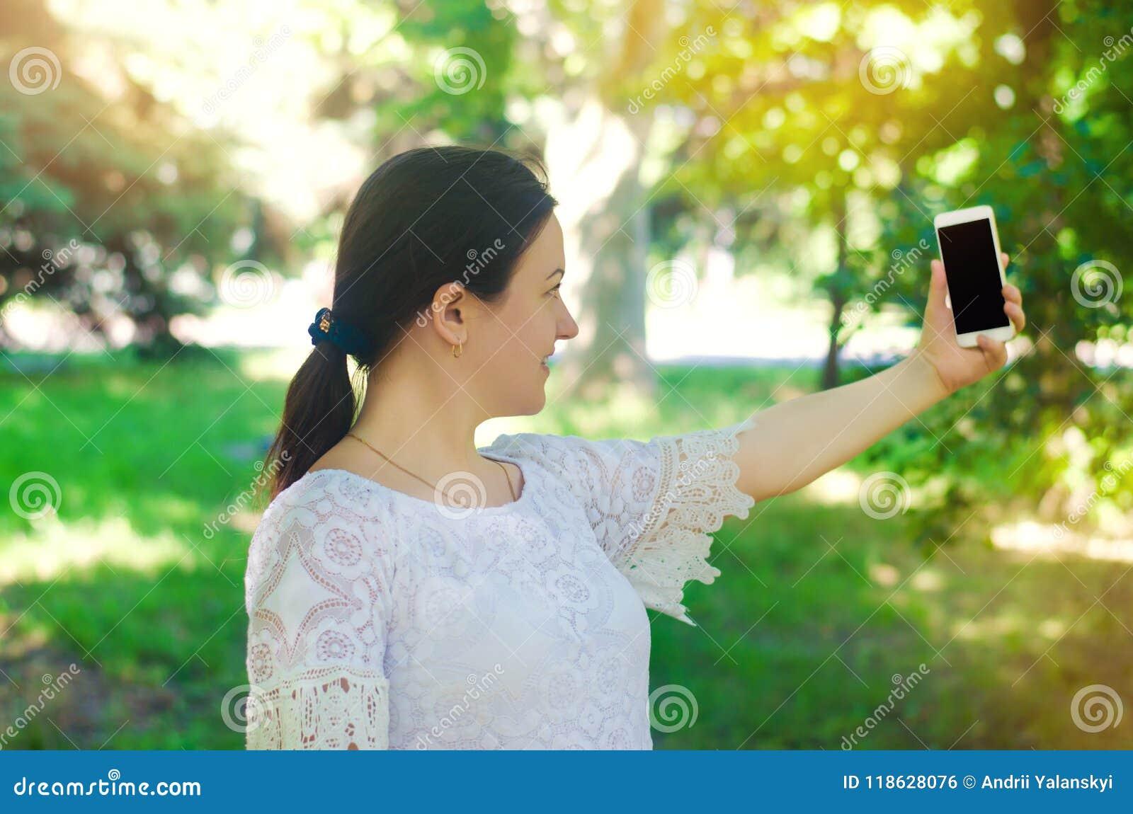 Красивое молодое европейское брюнет девушки фотографирует и делает selfie в парке города люди, образ жизни, идя внутри