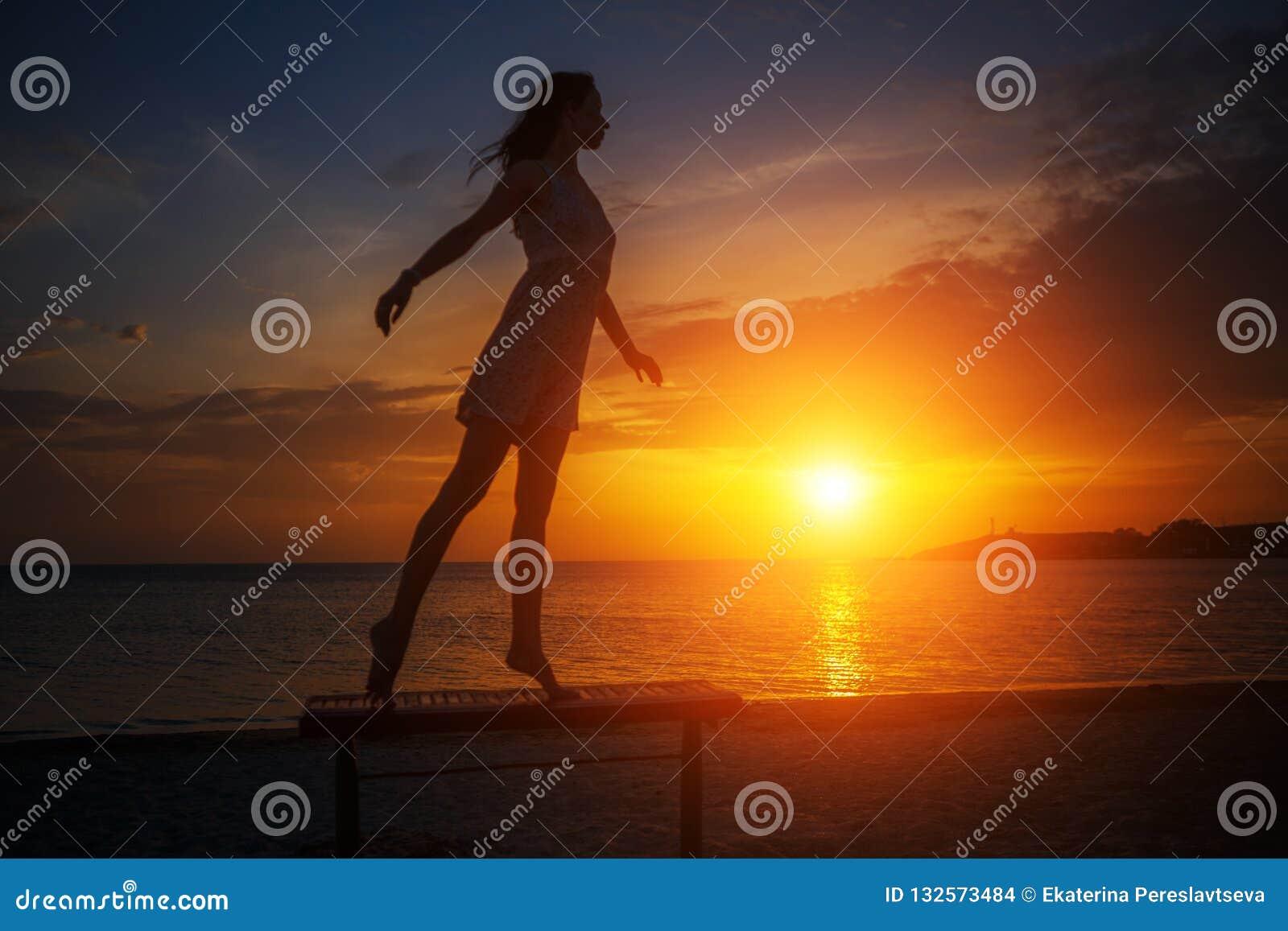 Красивое молодое худенькое положение женщины на пляже на заходе солнца, красивом силуэте против неба
