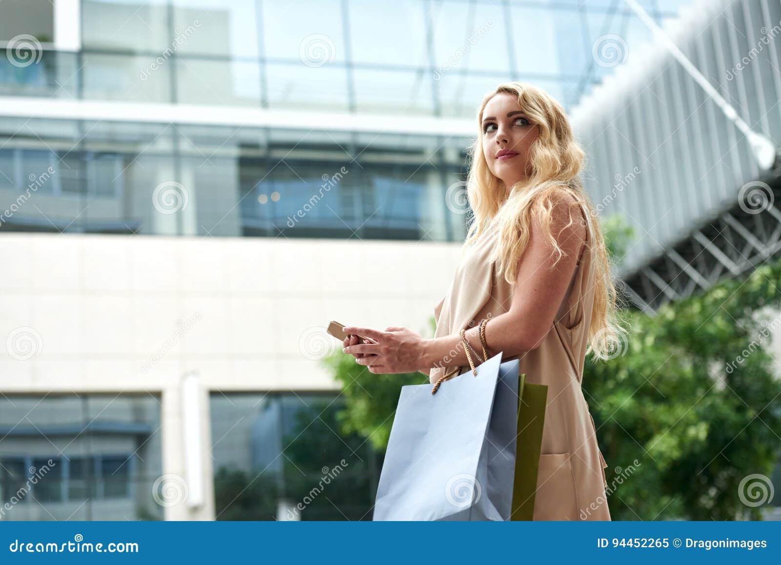 Красивое молодое белокурое используя Smartphone в улице