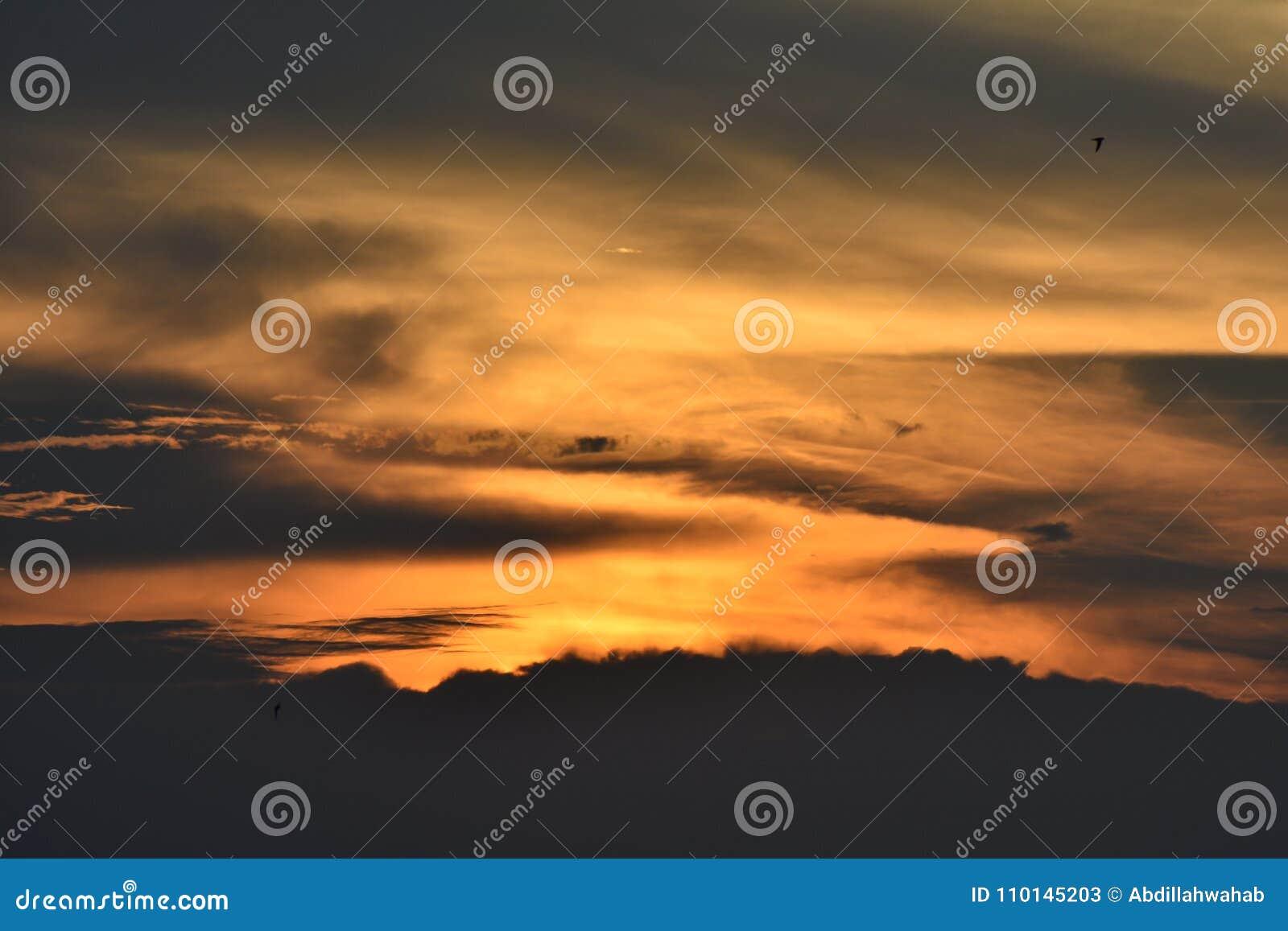 Красивое небо захода солнца, отраженное водой в озере