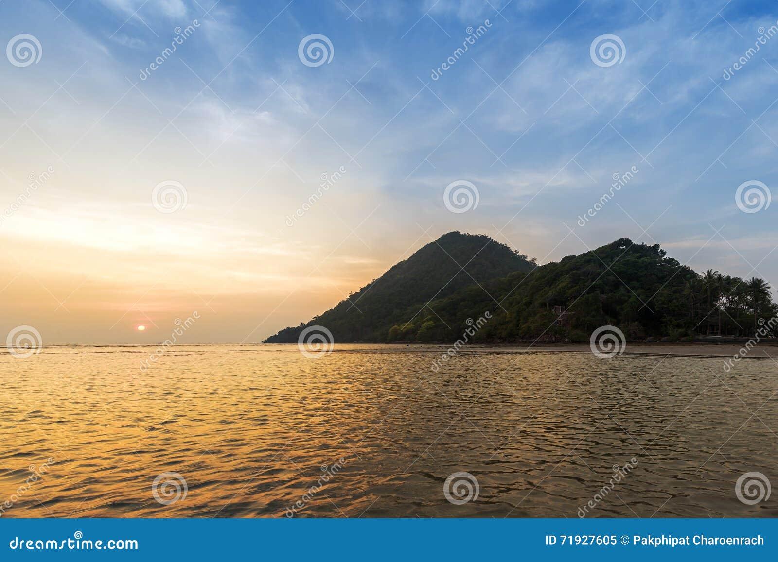 Красивое небо захода солнца над горой, морем и пляжем