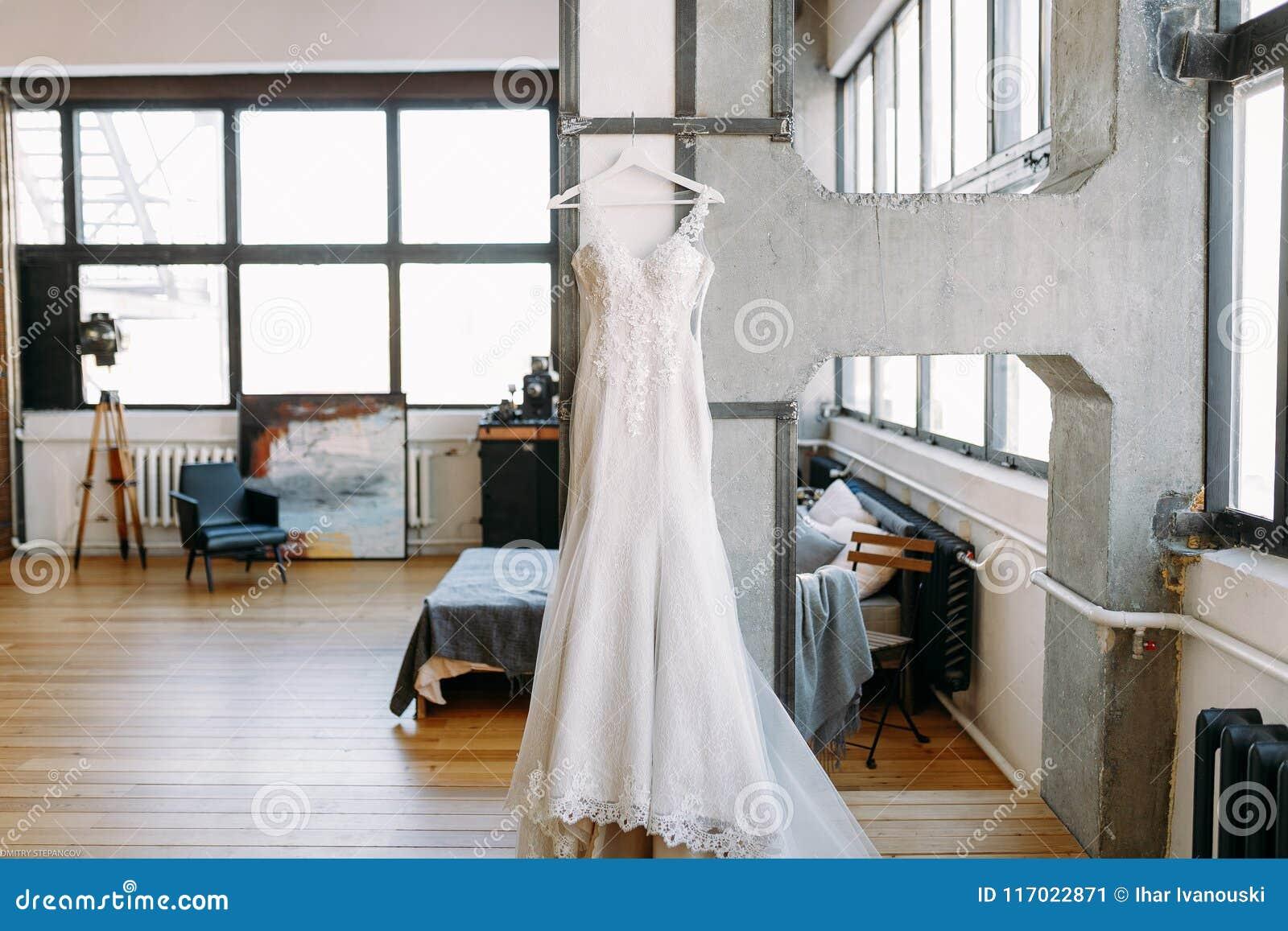 Красивое платье свадьбы женщин весит на вешалках в большой зале на стене
