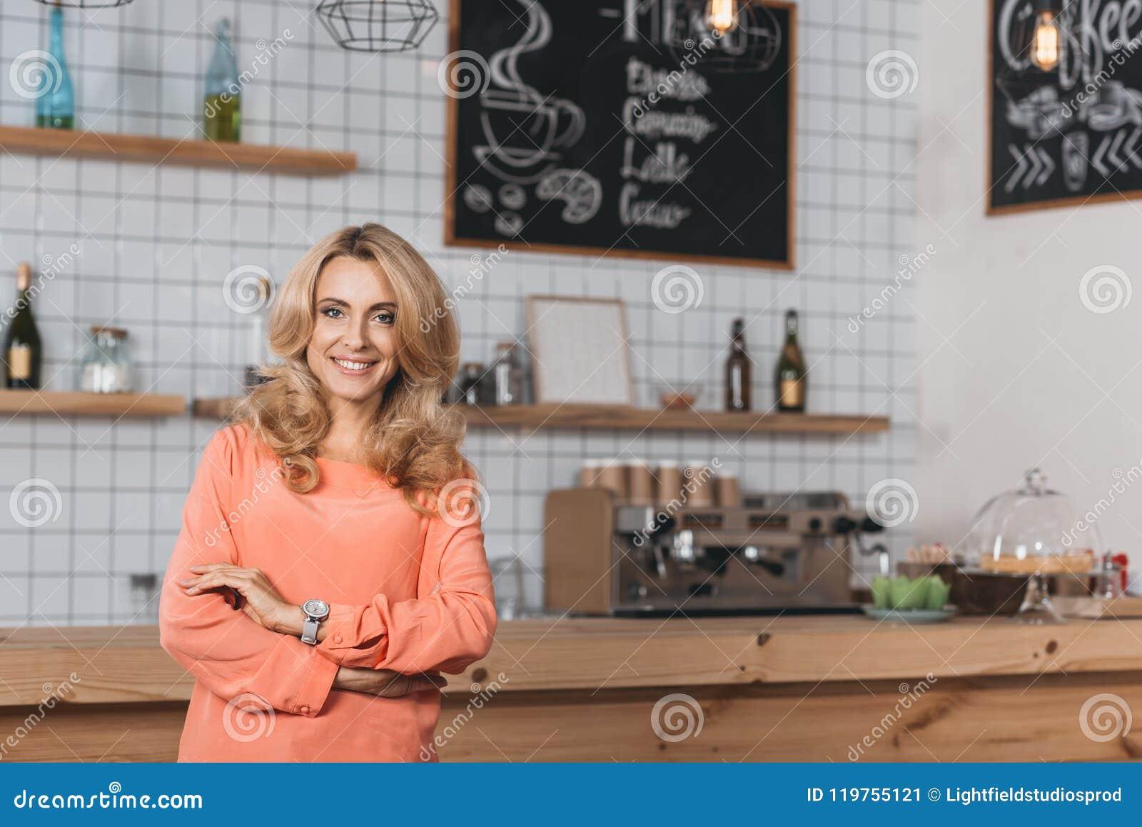 красивое предприниматель мелкого бизнеса усмехаясь на камере пока стоящ