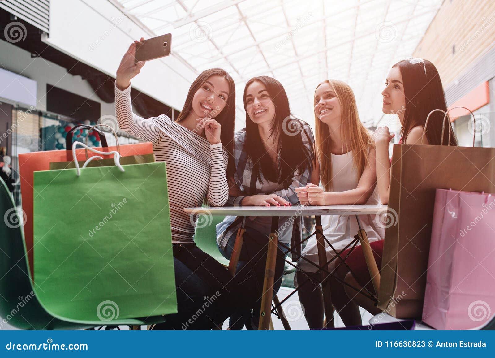 Красивые девушки сидят на таблице и говоря selfie Азиатская девушка держит камеру и фотографирует она там