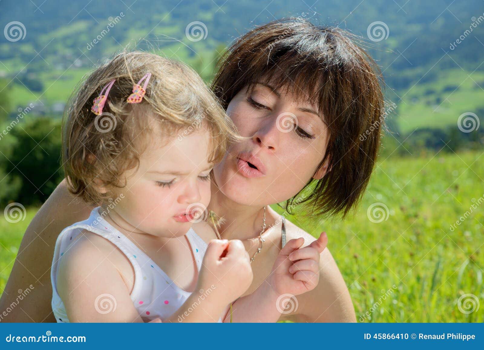 Красивые мама и дочь играют с цветком