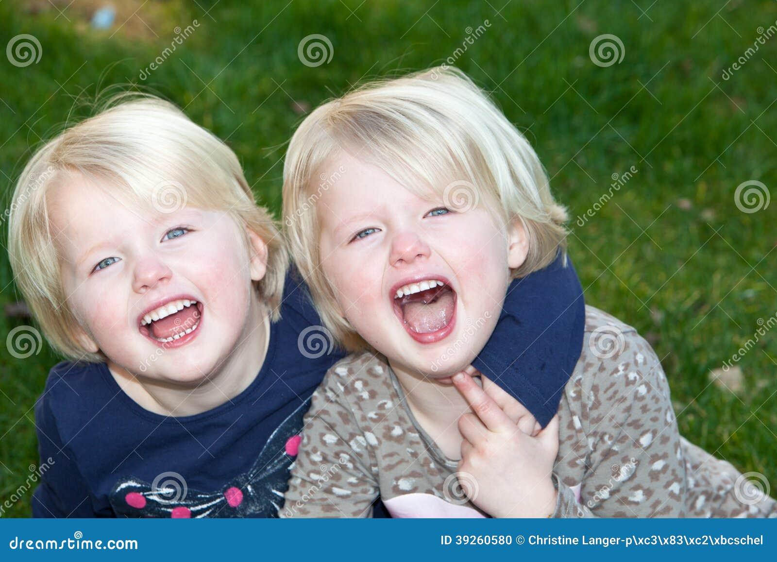 Красивые маленькие белокурые девушки идентичных близнцов