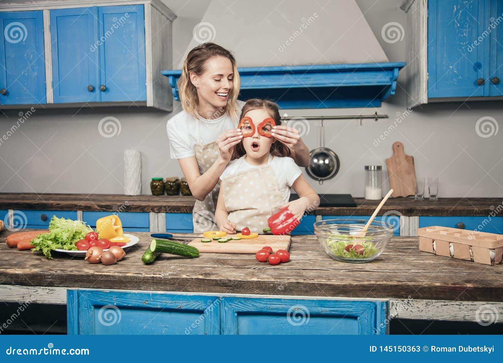 Красивые молодые мать и дочь имеют потеху пока подготавливающ их еду перед голубой кухней