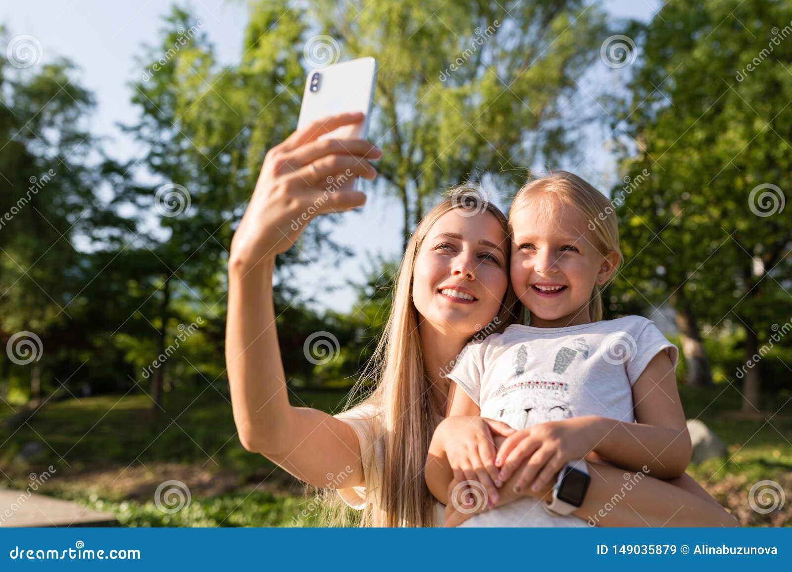 Красивые молодые мать и дочь со светлыми волосами используя мобильный телефон на открытом воздухе Стильные девушки делая selfie в