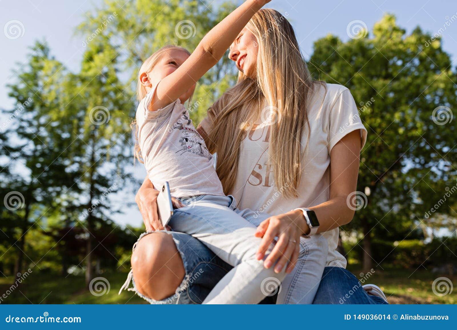 Красивые молодые мать и дочь с обнимать светлых волос на открытом воздухе Стильные девушки делая идти в парк r