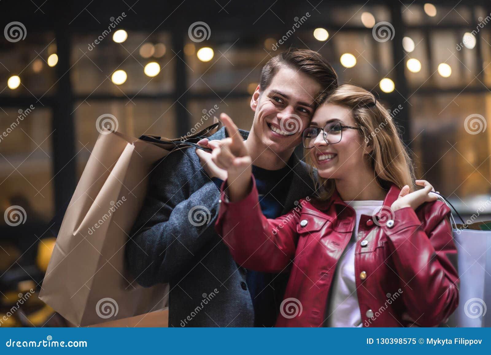 Красивые молодые пары наслаждаясь в покупках, имеющ потеху совместно Защита интересов потребителя, любовь, датируя, концепция обр