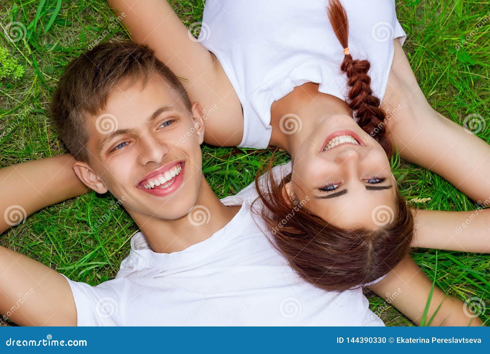 Красивые молодые пары на зеленой траве с улыбкой на стороне, счастливым отношением