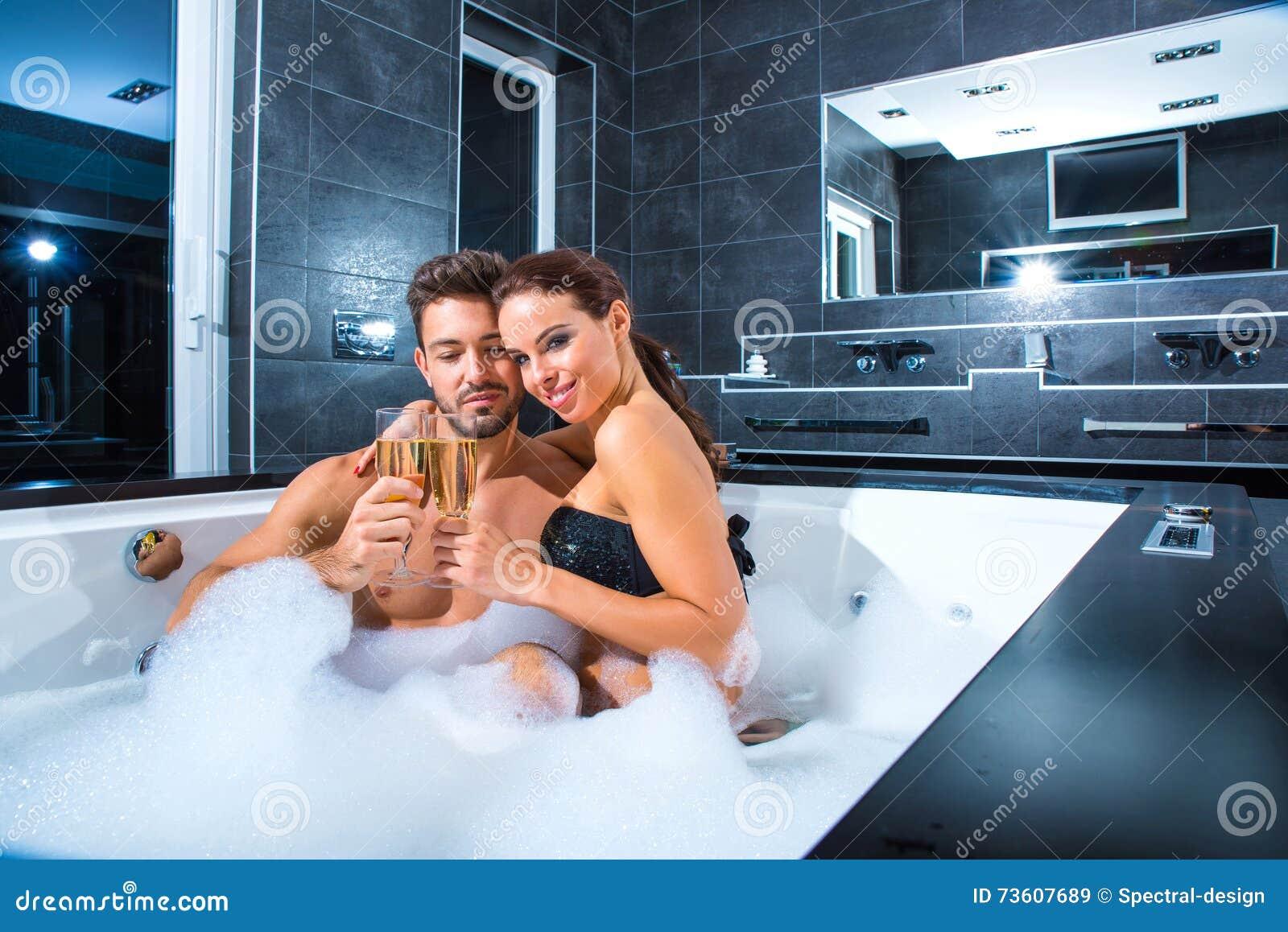 Красивые молодые пары выпивая Шампань в водовороте