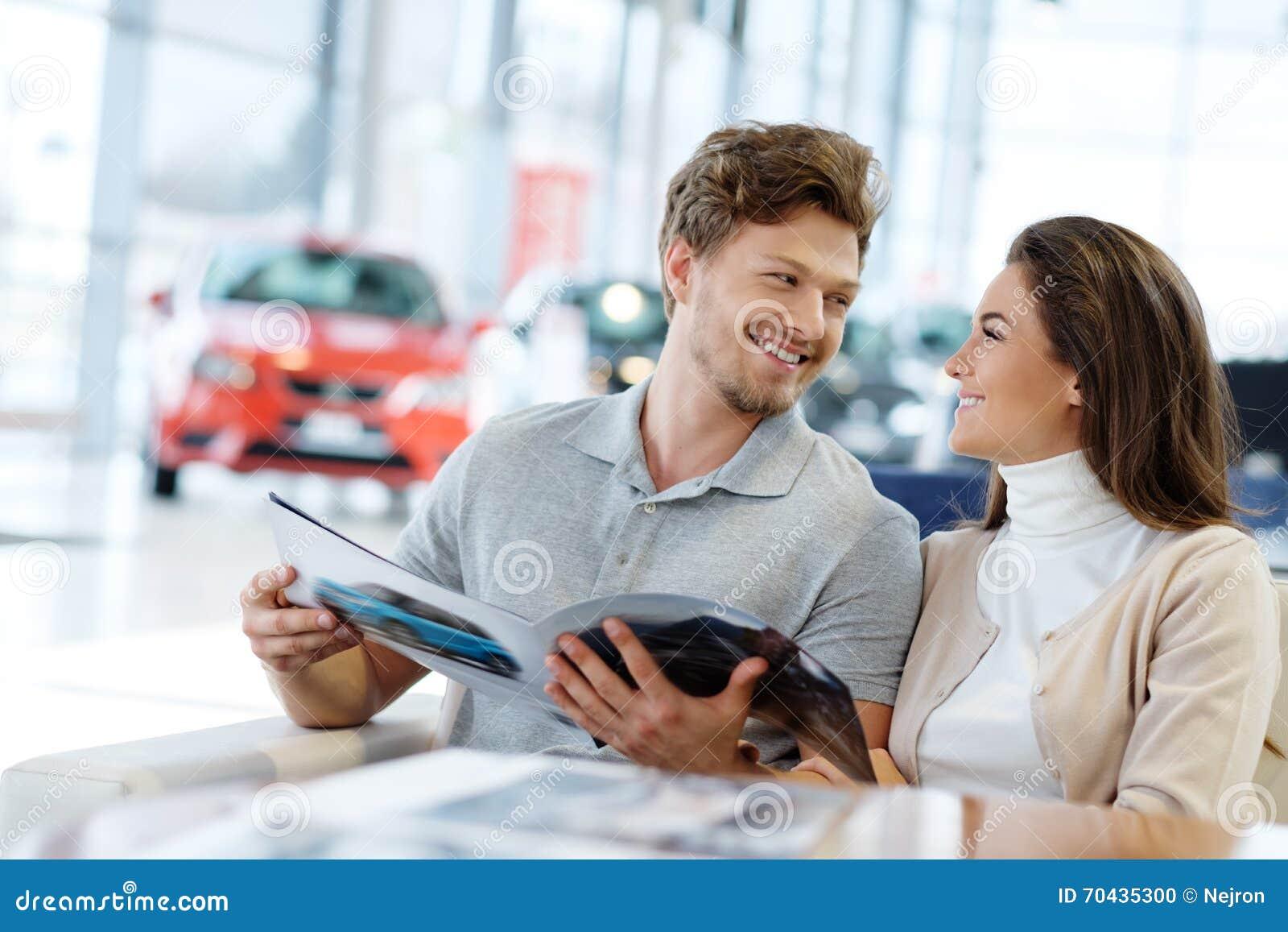 Красивые молодые пары смотря новый автомобиль на выставочном зале дилерских полномочий