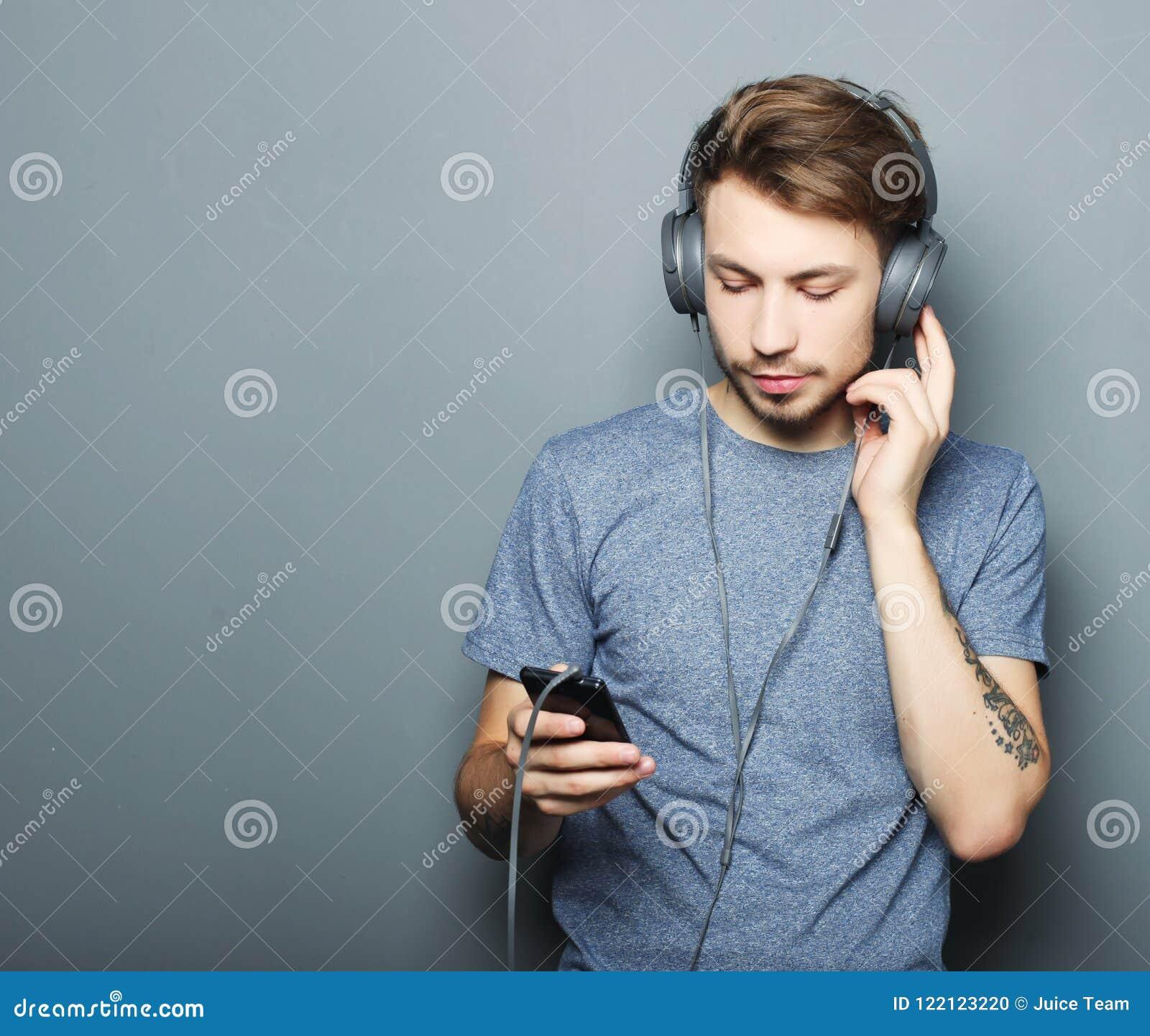 Красивые наушники молодого человека нося и мобильный телефон держать пока стоящ против серой стены