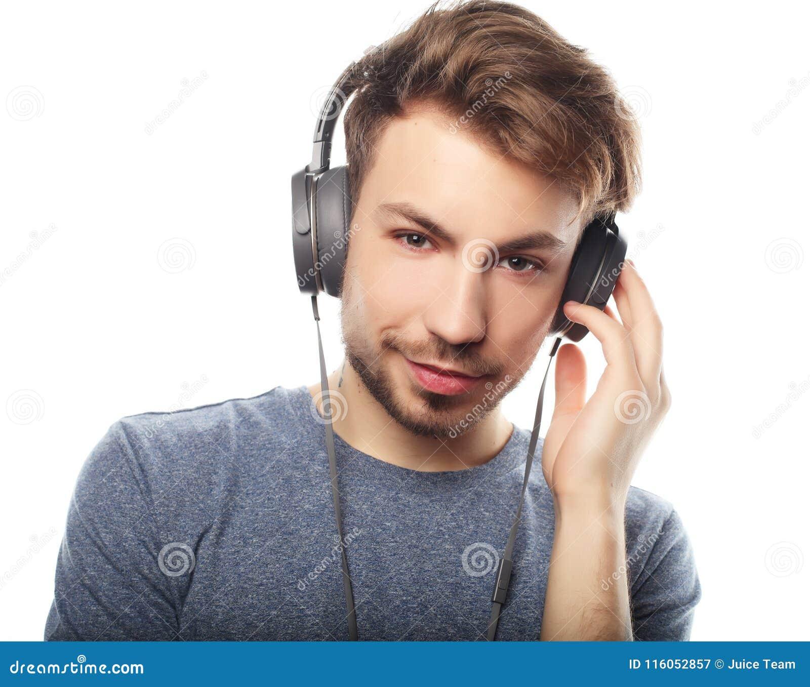 Красивые наушники молодого человека нося и слушать к музыке