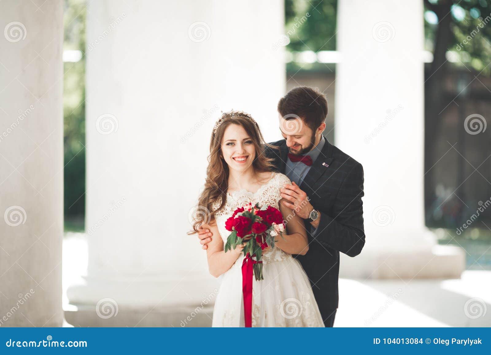 Красивые пары, жених и невеста представляя около большого белого столбца