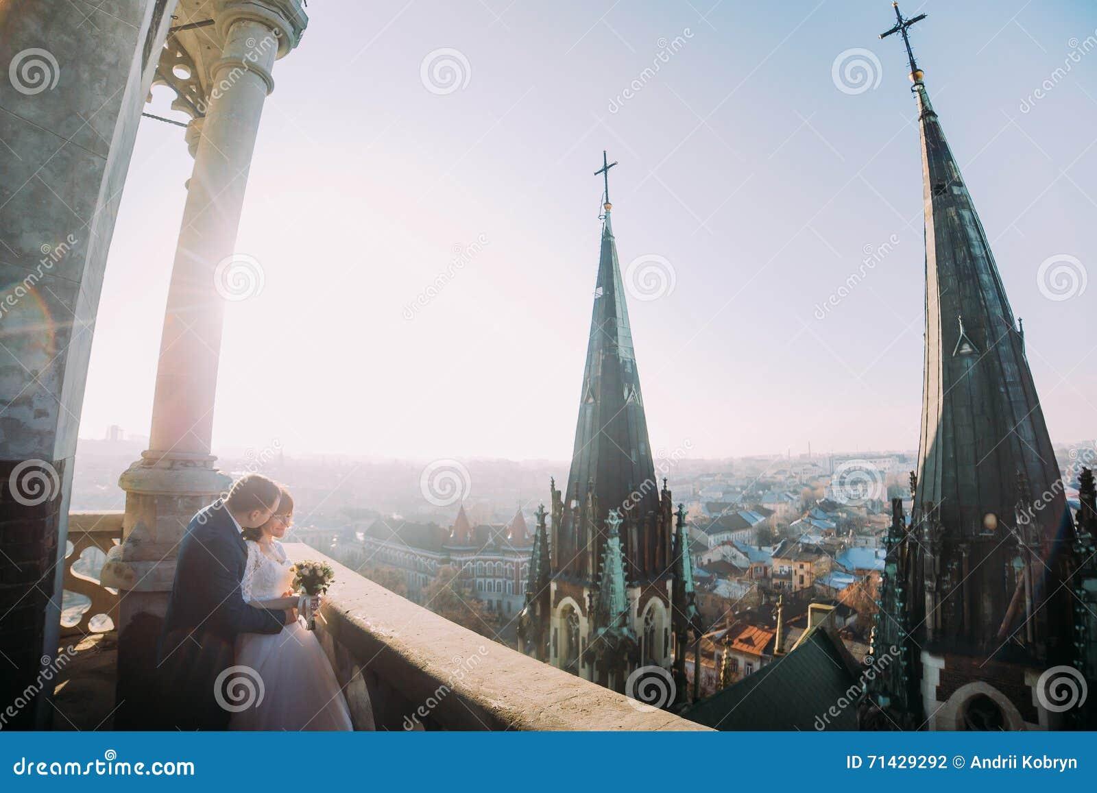 Красивые пары, жених и невеста представляя на старом балконе с столбцом, предпосылкой городского пейзажа