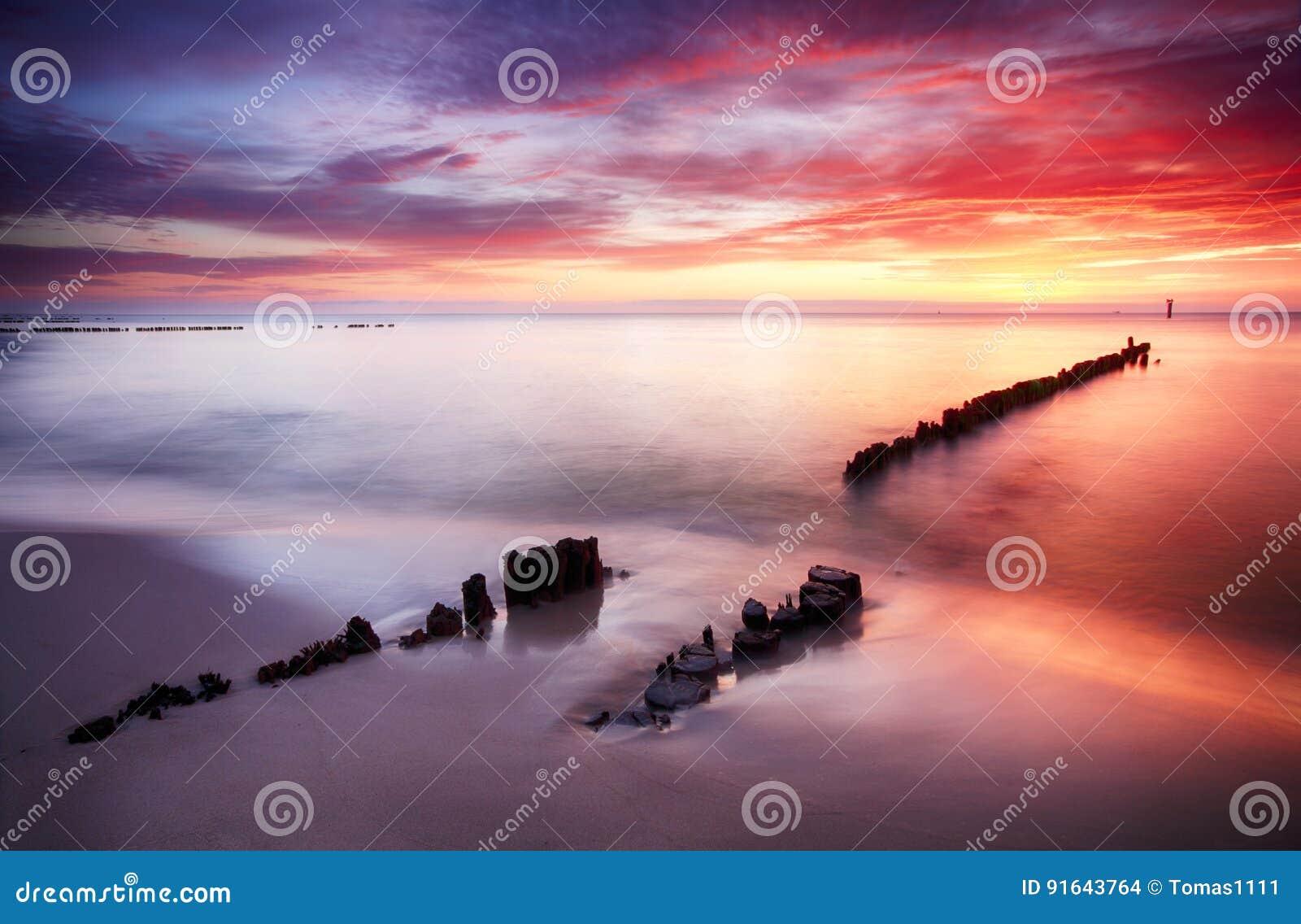 Красивые покрашенные облака над океаном на пляже на заходе солнца